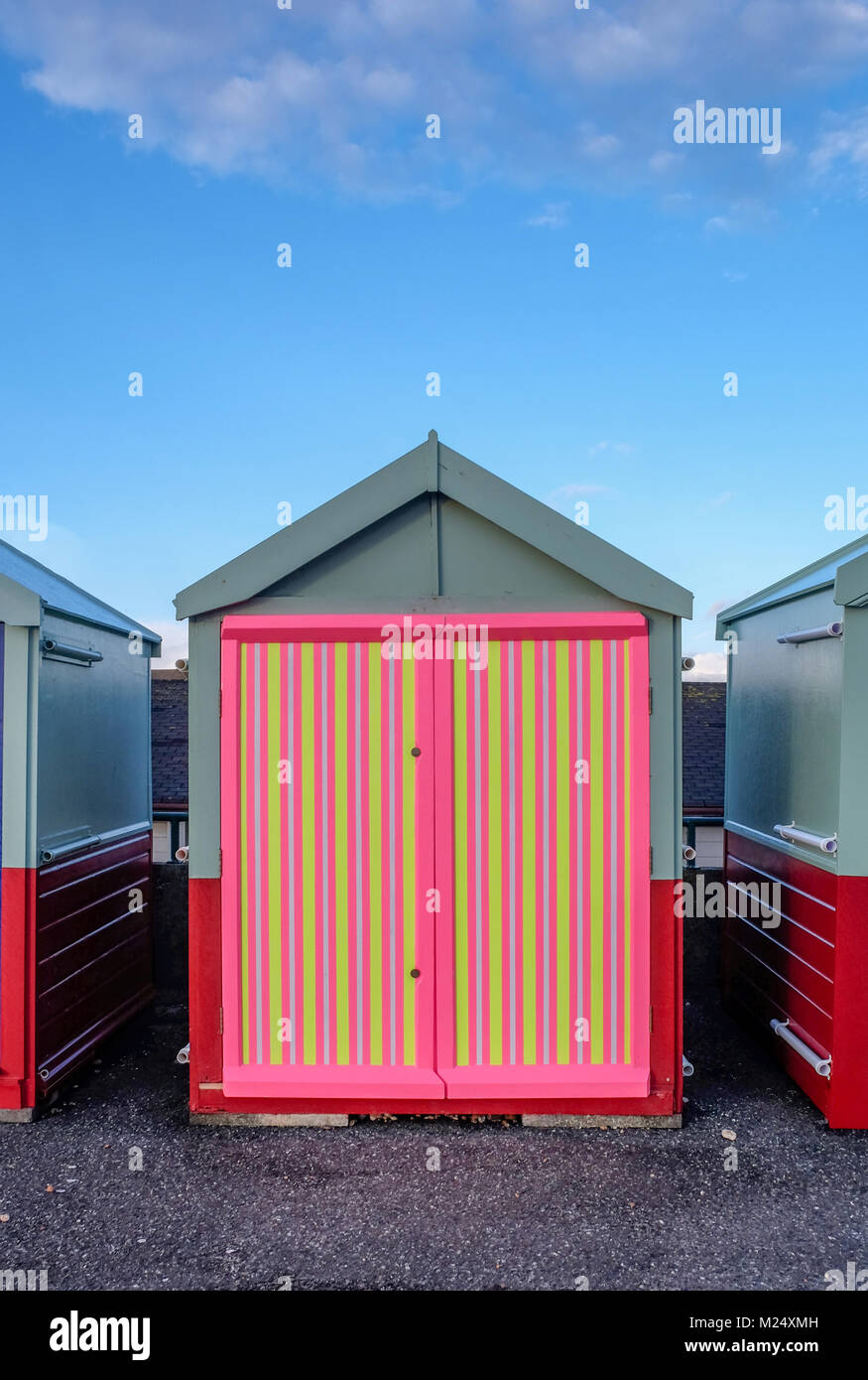 Brighton beach hut with a multi coloured door of yellow, pink, black stripes behind is blue sky and infront is the - Stock Image