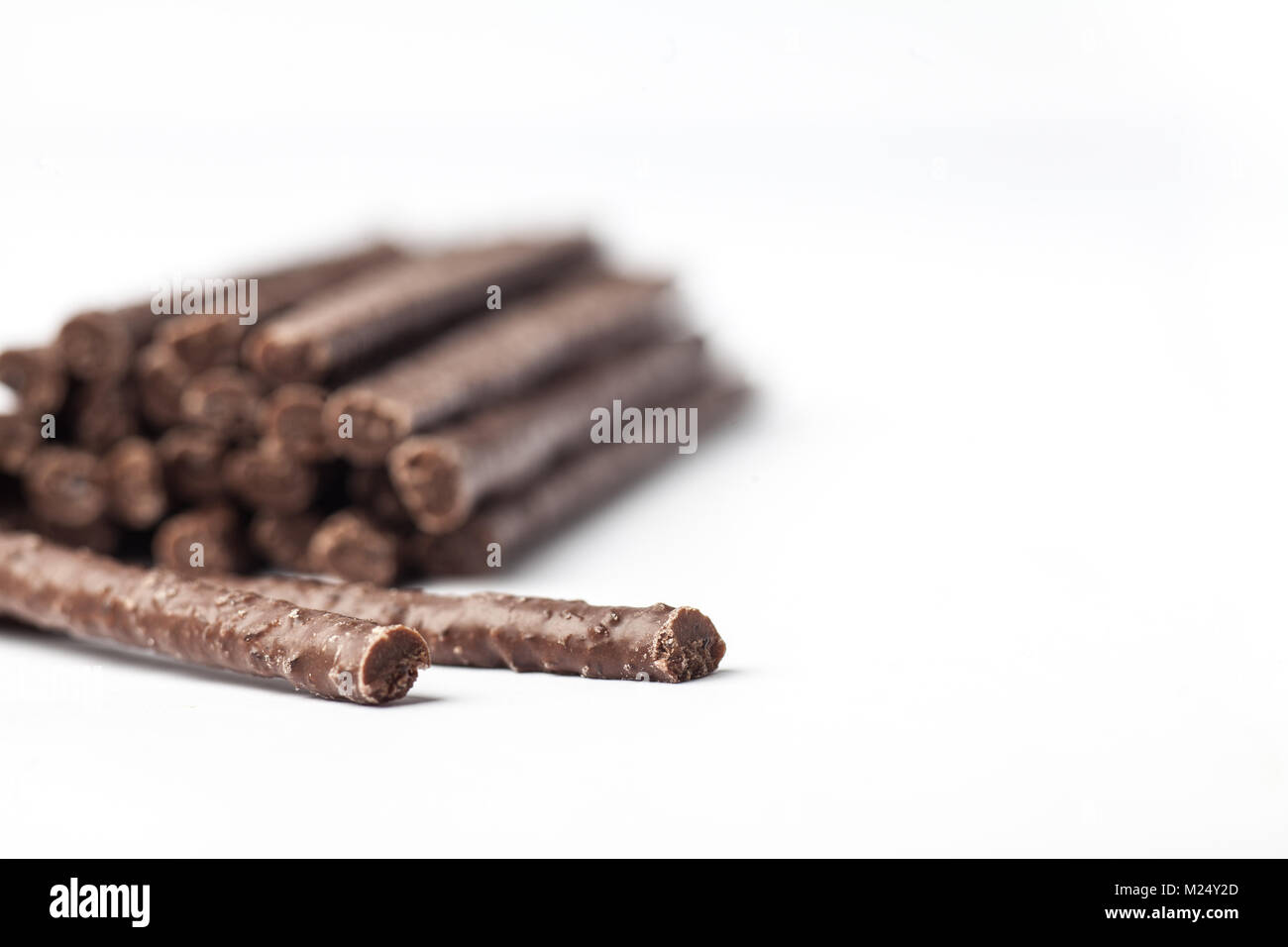 Chocolate Flavoured Stick Candy close up with pile in background - Stock Image