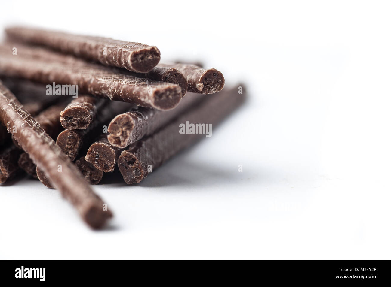 Chocolate Flavoured Stick Candy close up on white background - Stock Image