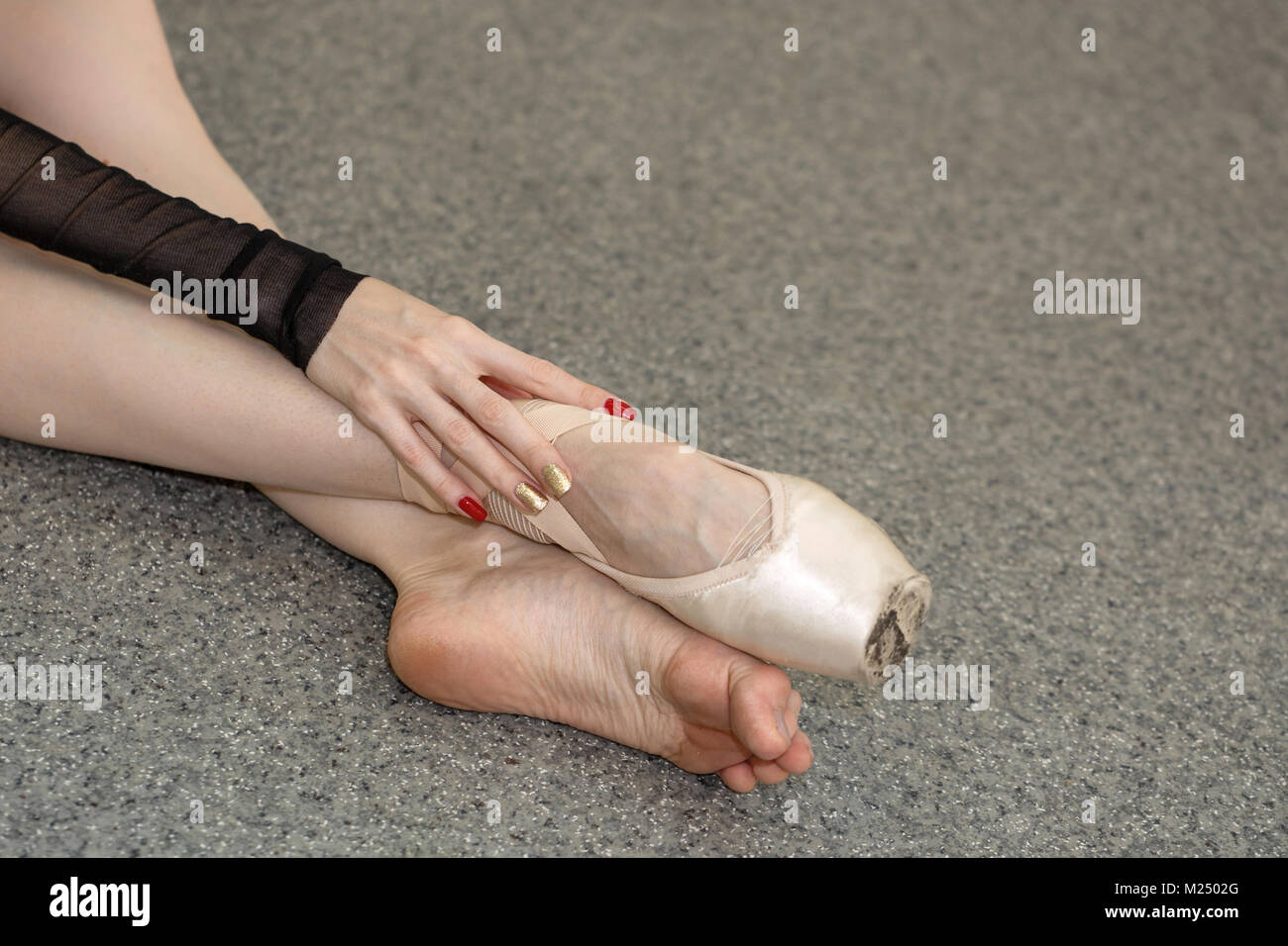 The ballerina wore a pointe with one foot. Slender long female legs. Shooting close-ups - Stock Image