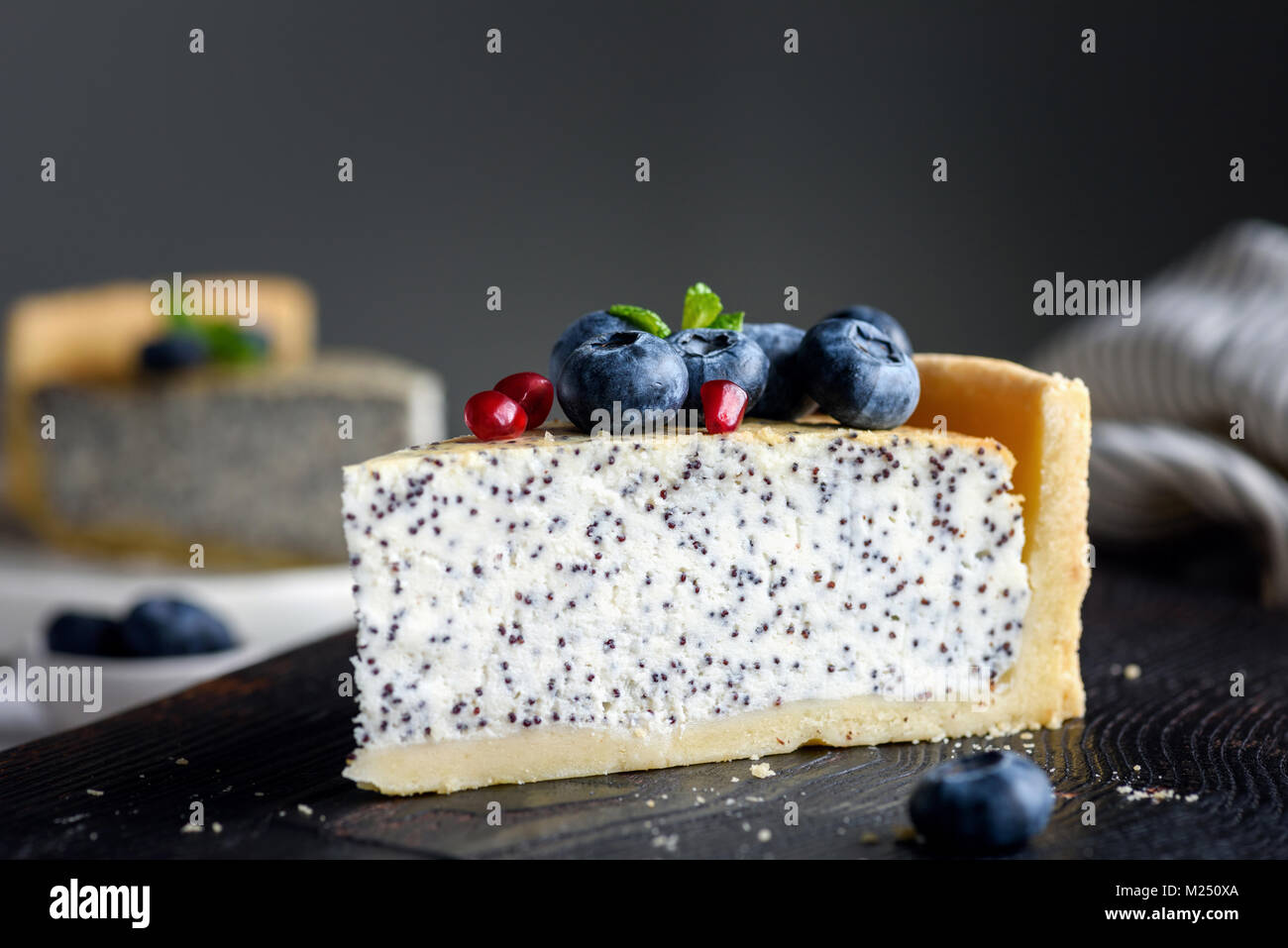 Slice of cheesecake with poppy seeds decorated with fresh blueberries, pomegranate seeds and mint. Selective focus - Stock Image