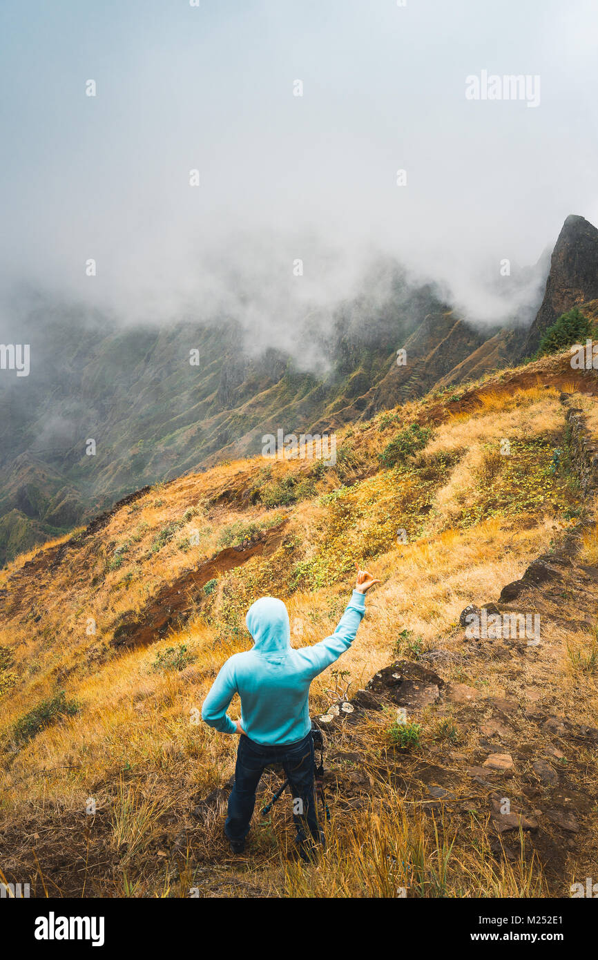 Traveler staying on the cobbled path and admiring clouds flowing over the mountain peaks into the valley. Santo Stock Photo