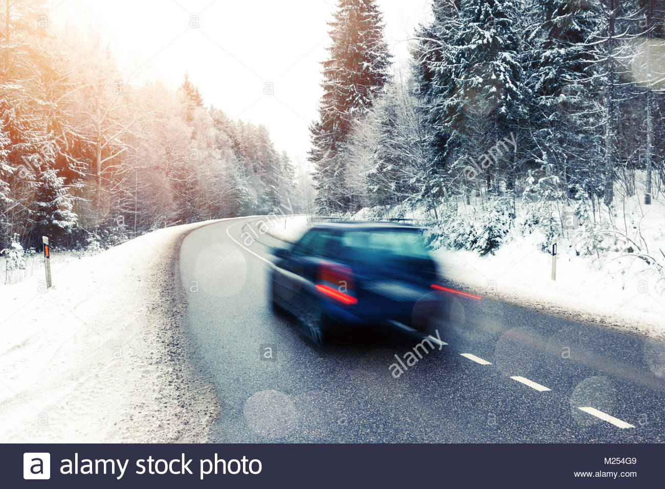 Lonely car in motion blur on the road in winter landscape with sunset and glowing light overlays - Stock Image