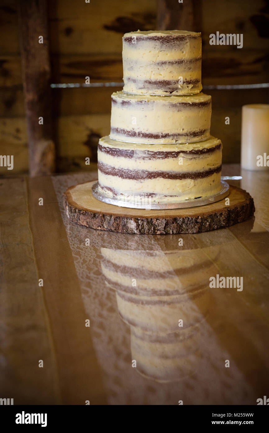 Three tiered celebration cake on wooden table - Stock Image