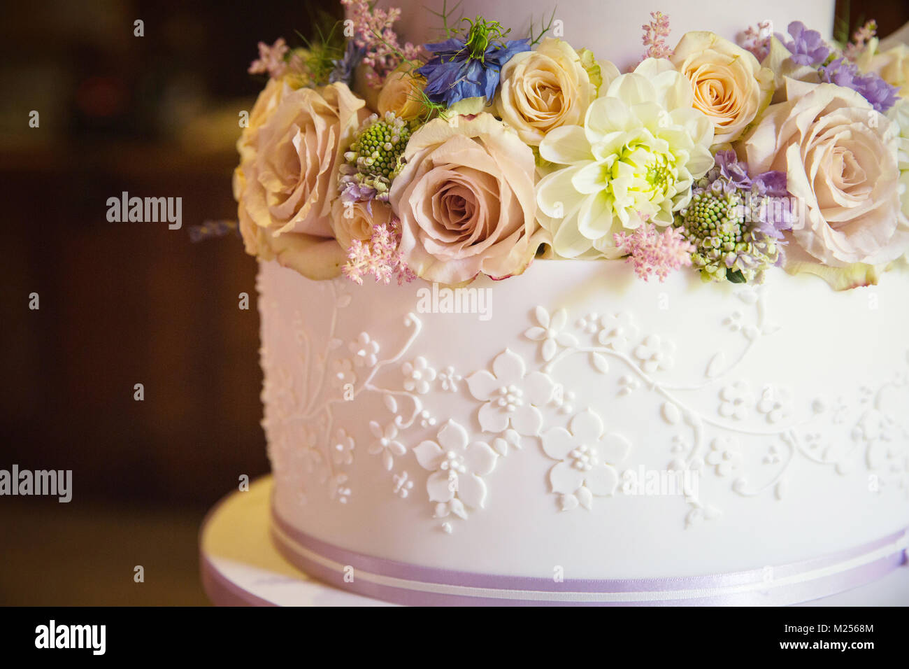 Fresh flowers on tier of wedding cake, close up - Stock Image