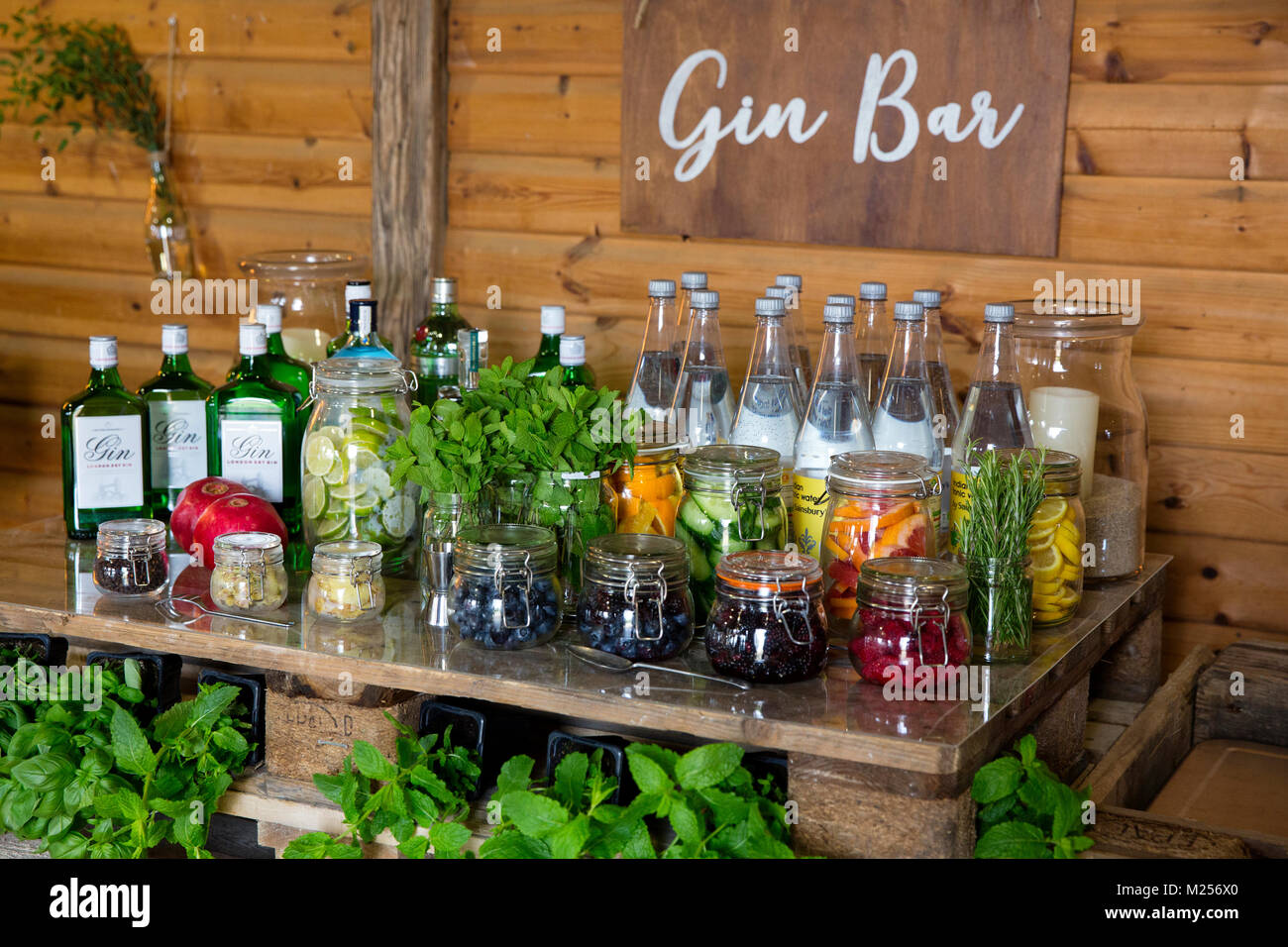 Gin bar in barn with bottled gin, tonic water and jars - Stock Image