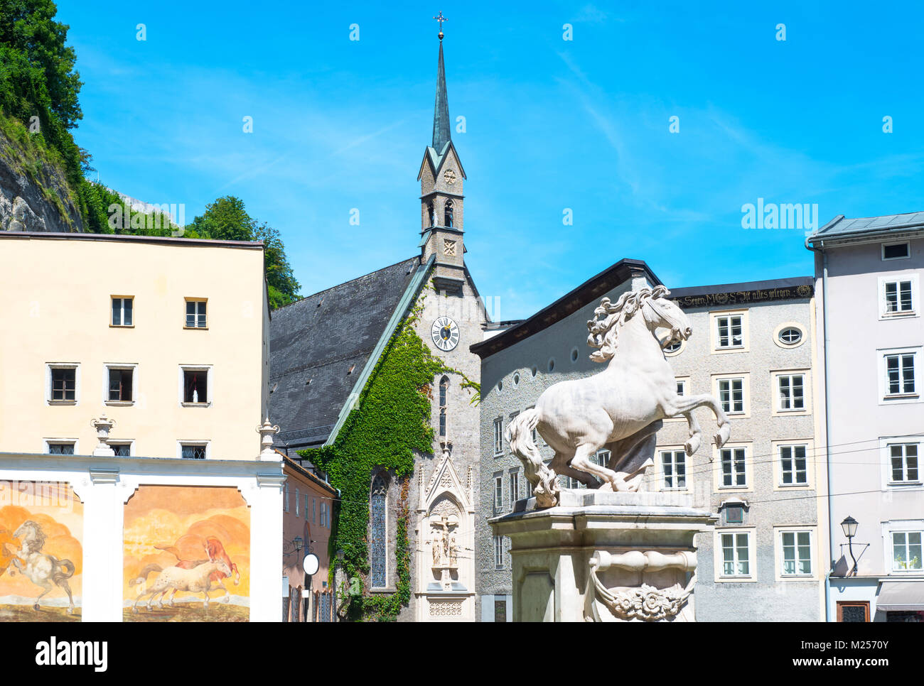 Austria, Salzburg, the Pferde Schwahme equestrian fountain with the St Blasius church in the background - Stock Image