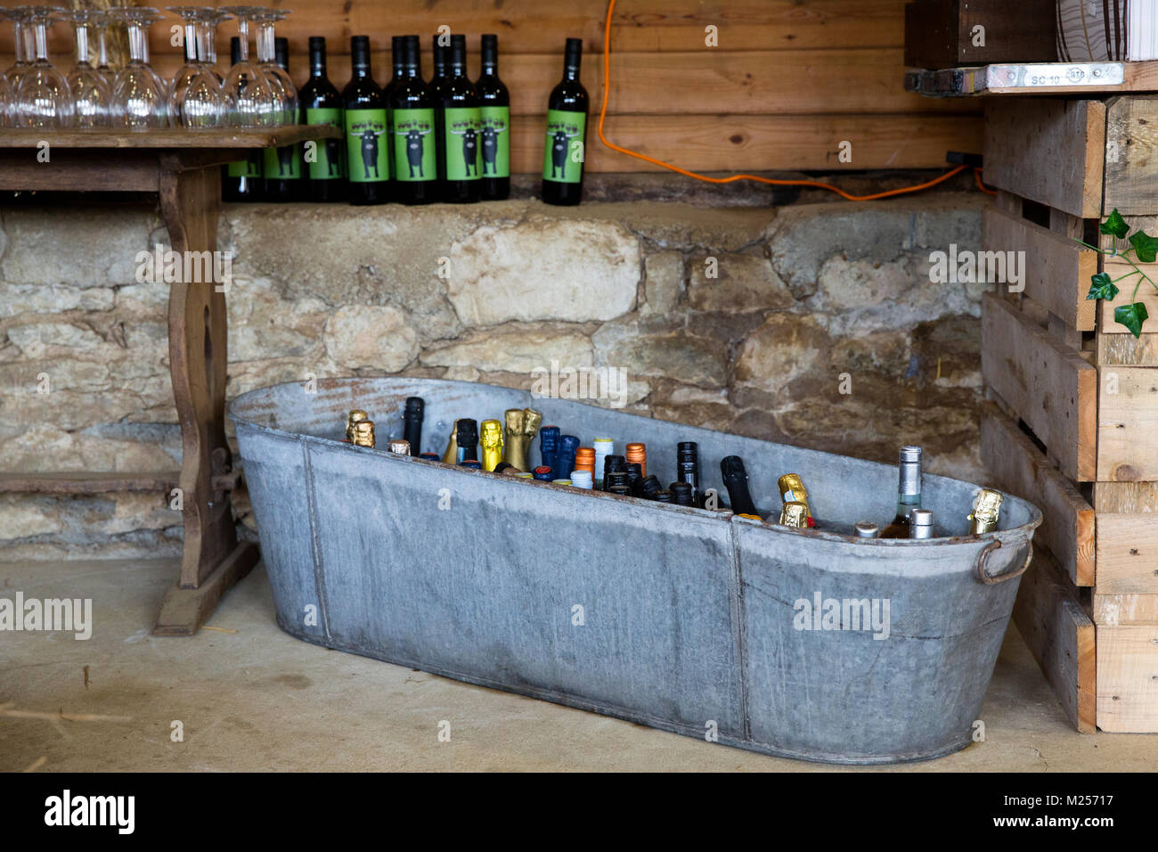Barn with tin bath full of bottle of drink, beer bottles and wooden table with glasses - Stock Image