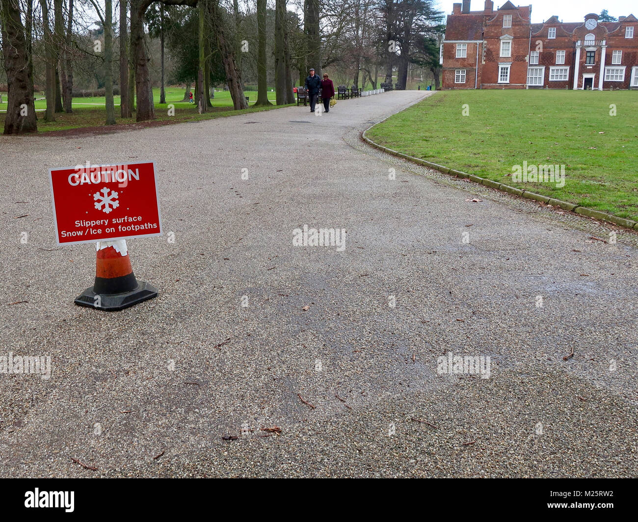 Caution snow / ice slippery surface warning notice out in Christchurch Park after a cold and snowy night. Snow has - Stock Image