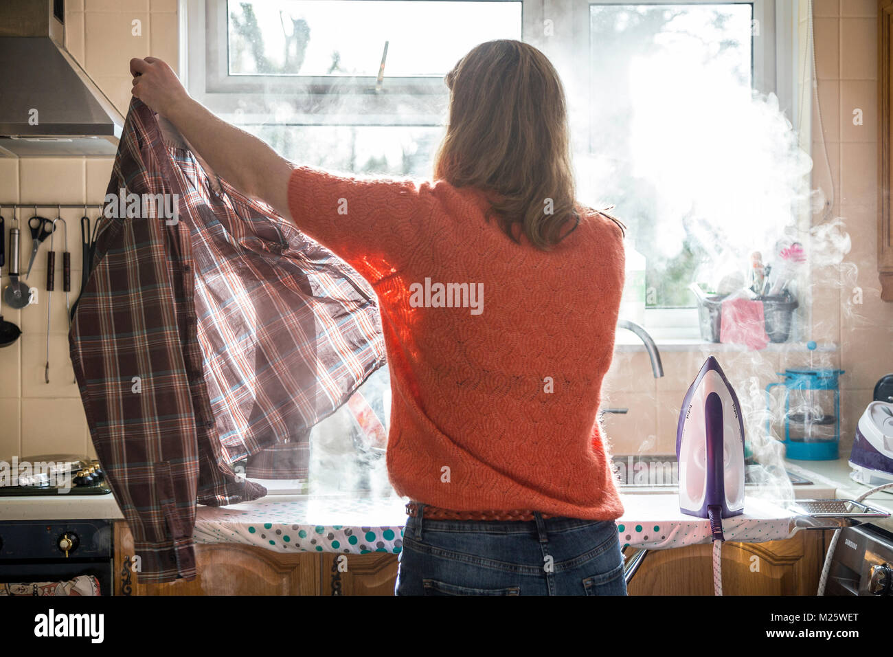 young mum irons check shirt in Kitchen,activity or task of ironing clothes, sheets,tailoring backstitching,A female - Stock Image