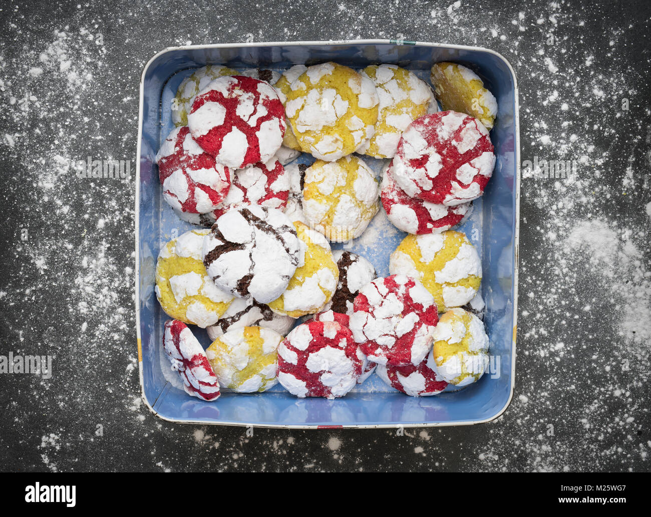 Homemade Lemon, Raspberry and Chocolate Crinkle Cookies in a tin on slate background - Stock Image