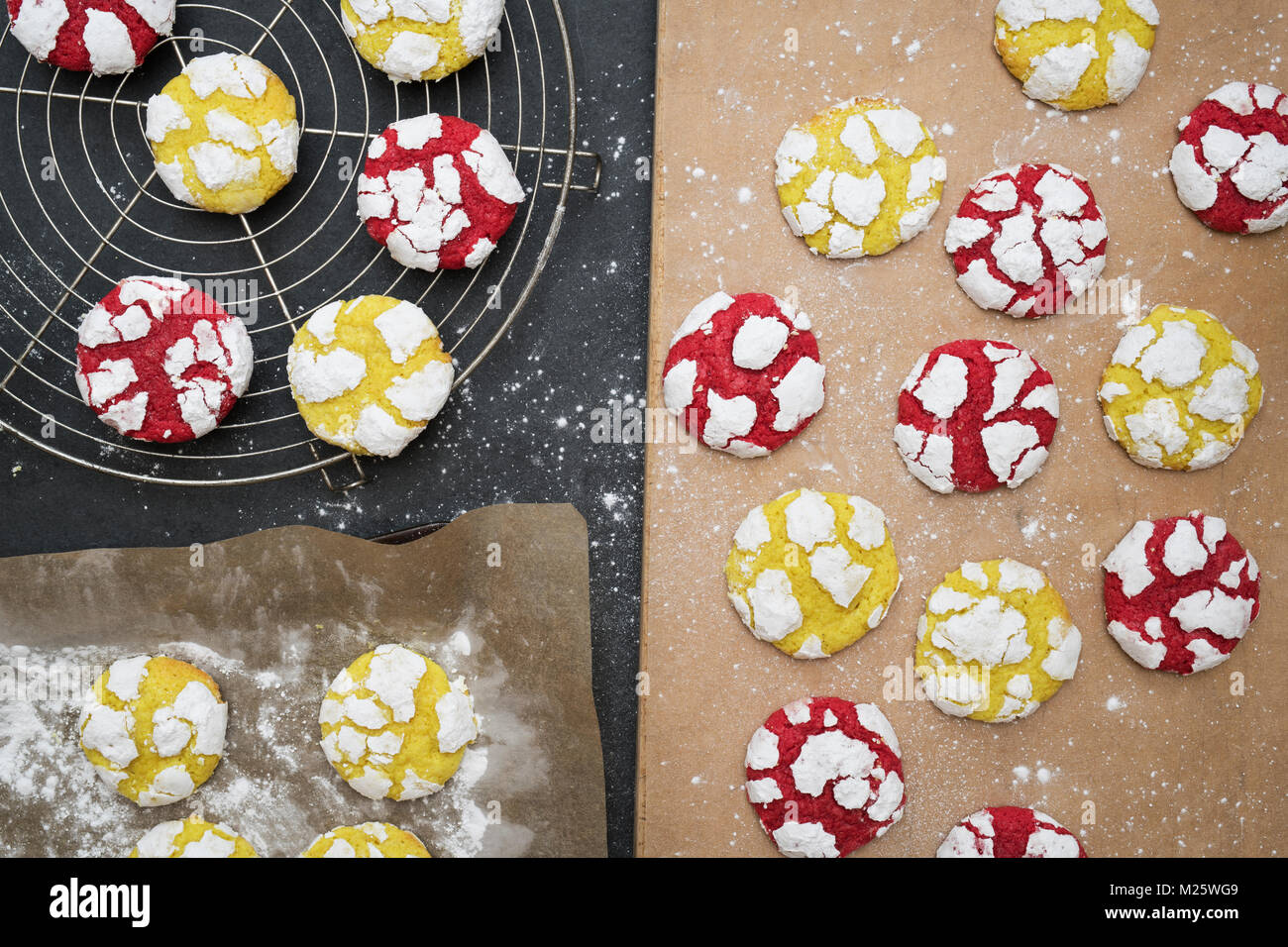 Homemade Lemon and Raspberry Crinkle Cookies on a cooling rack on slate background - Stock Image