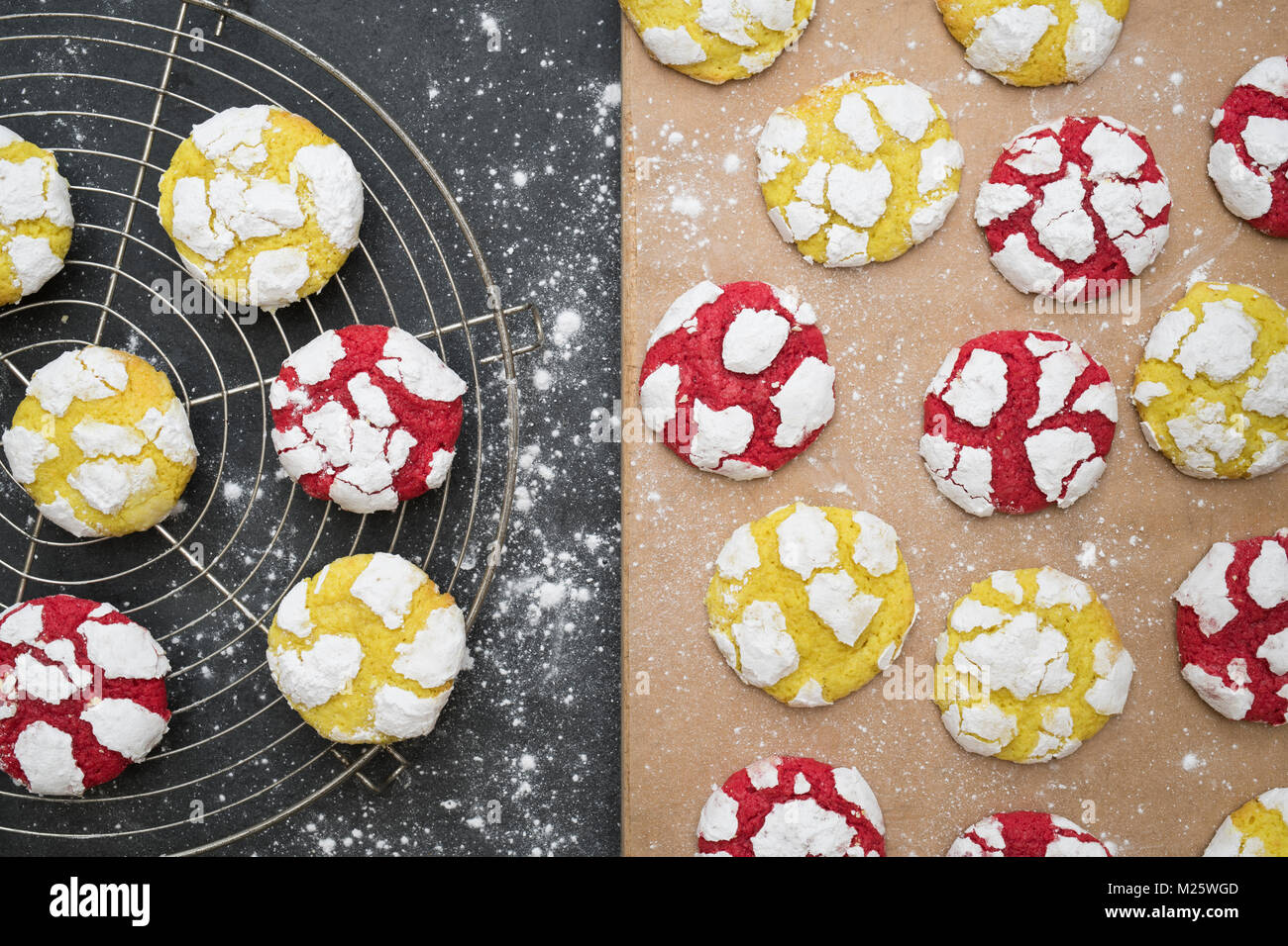 Homemade Lemon and Raspberry Crinkle Cookies on a cooling rack on slate background Stock Photo