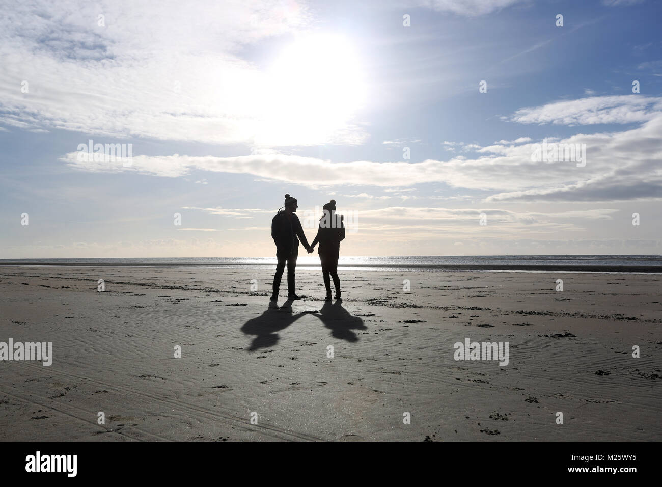 A couple pictured holding hands and walking along the beach in West Wittering, West Sussex, UK. - Stock Image
