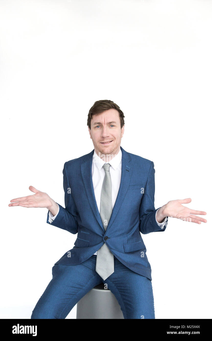 portrait of a smartly dressed man who is shrugging his shoulders with his Palme up in a confident fashion. Isolated - Stock Image