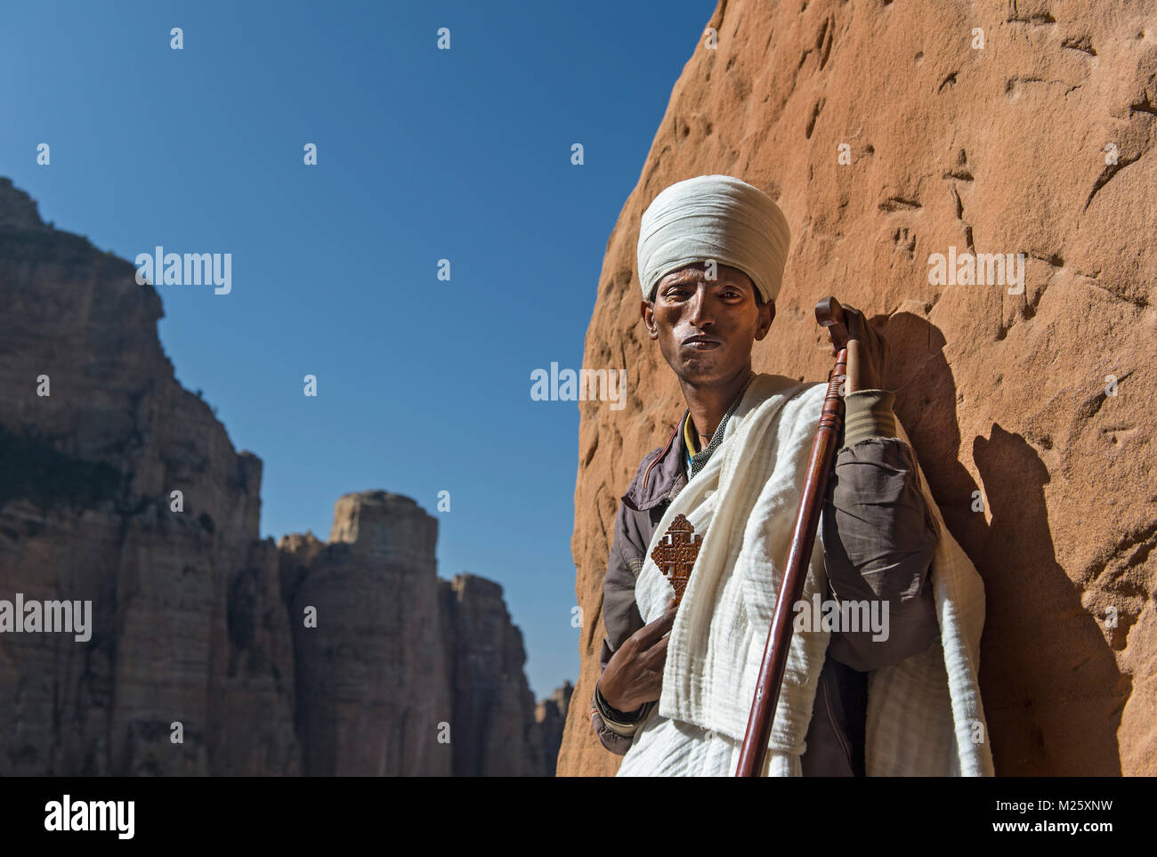 Coptic priest standing at the entry to the rock-hewn church Abuna Yemata situated high up at a steep rock pinnacle, - Stock Image