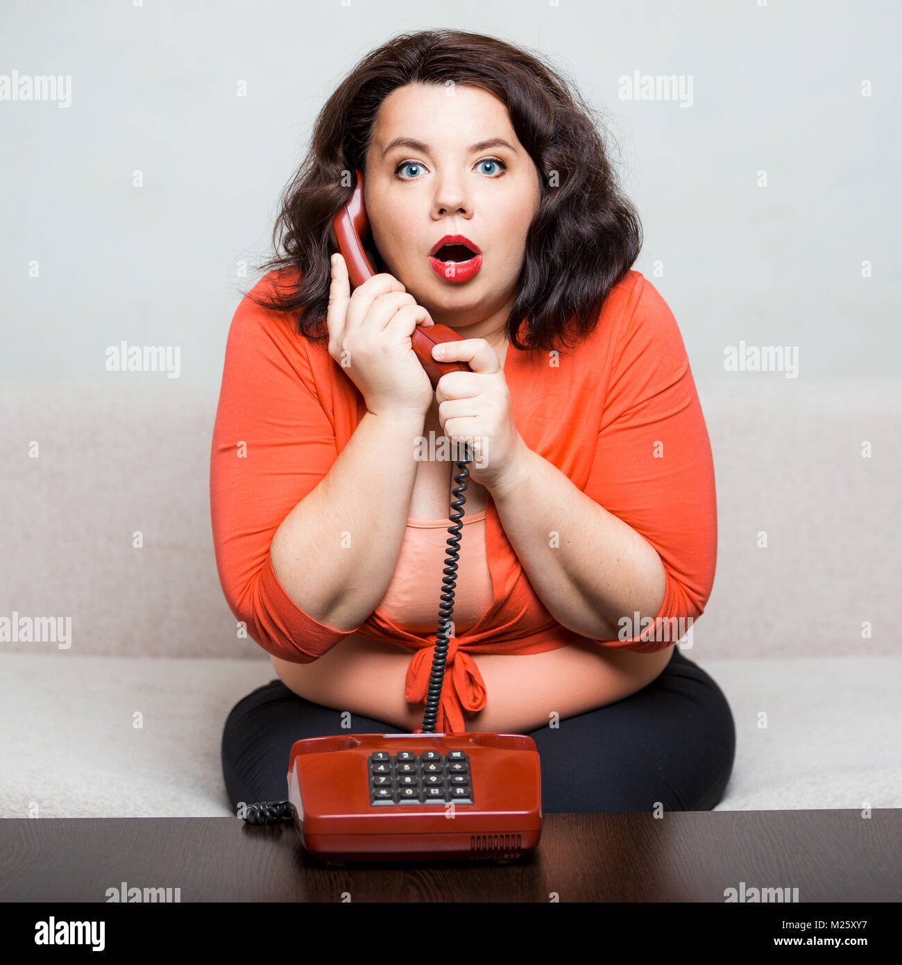 Portrait of a surprised fat adult woman with a phone - Stock Image