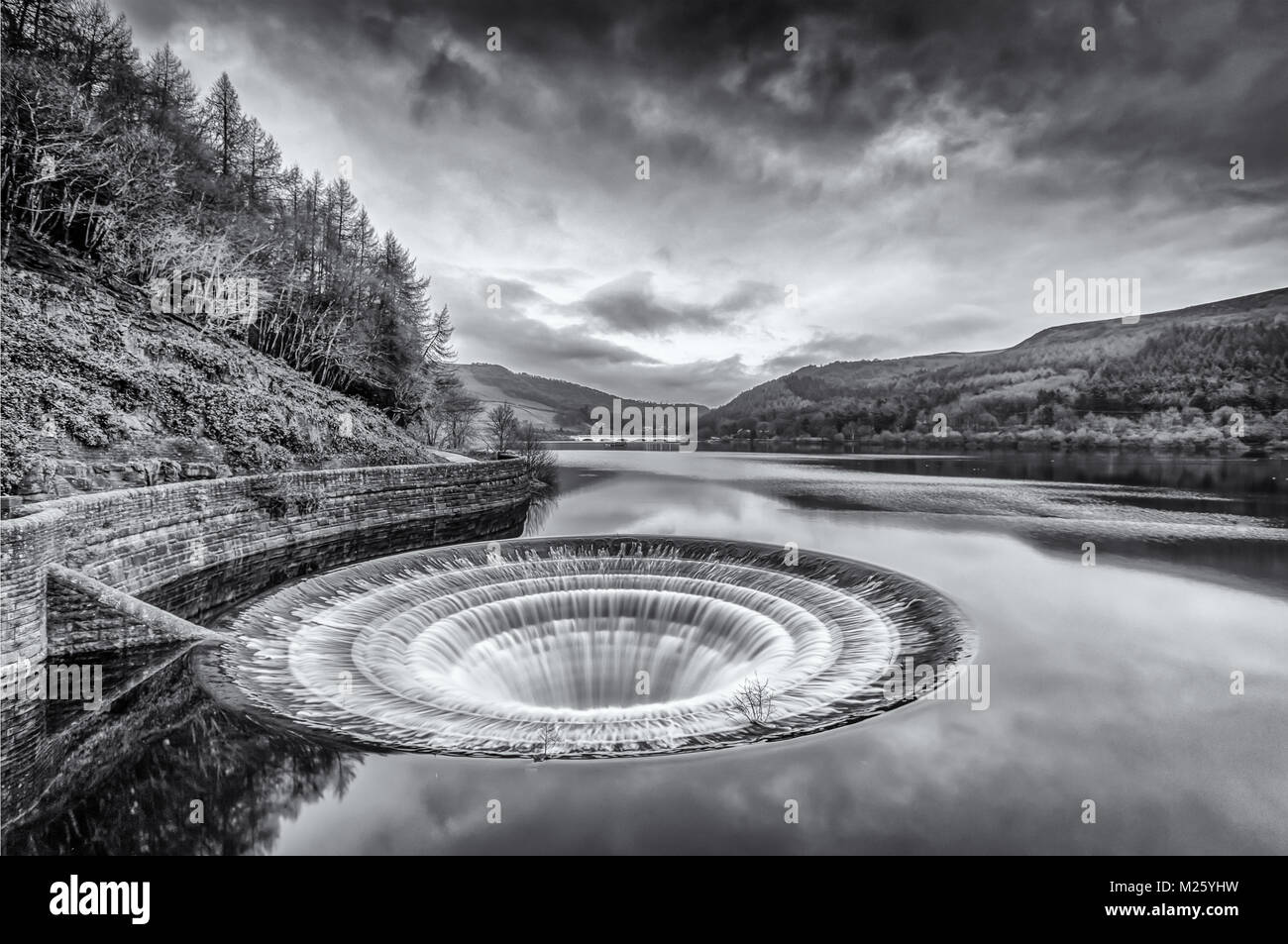 The 'plughole' at Ladybower reservoir in the Peak District.  Showing at full flow on a cold, overcast day. - Stock Image
