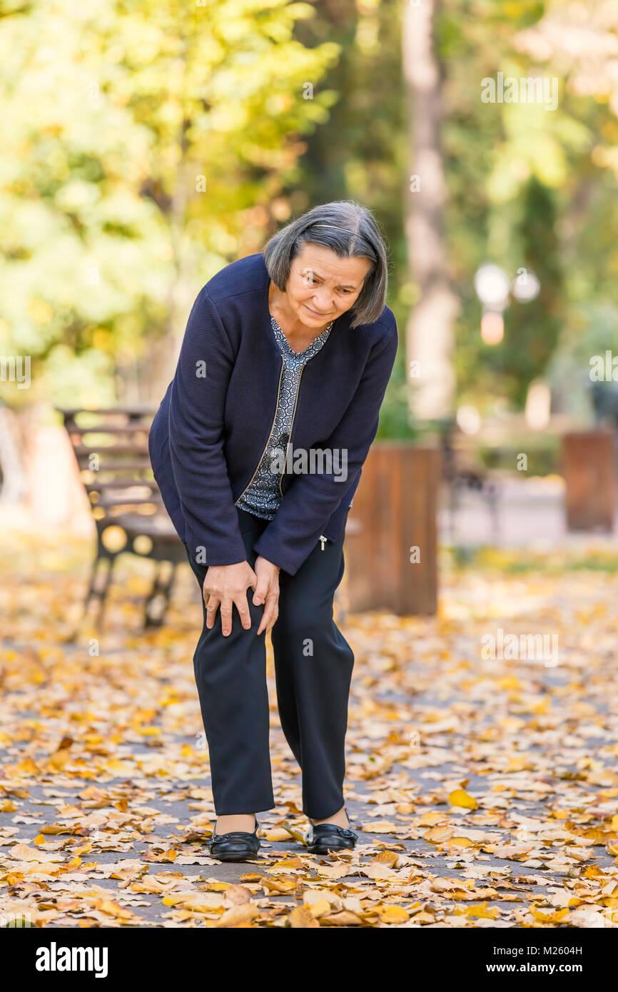 Senior woman walking in autumn park and having knee pain. Arthritis pain concept. - Stock Image