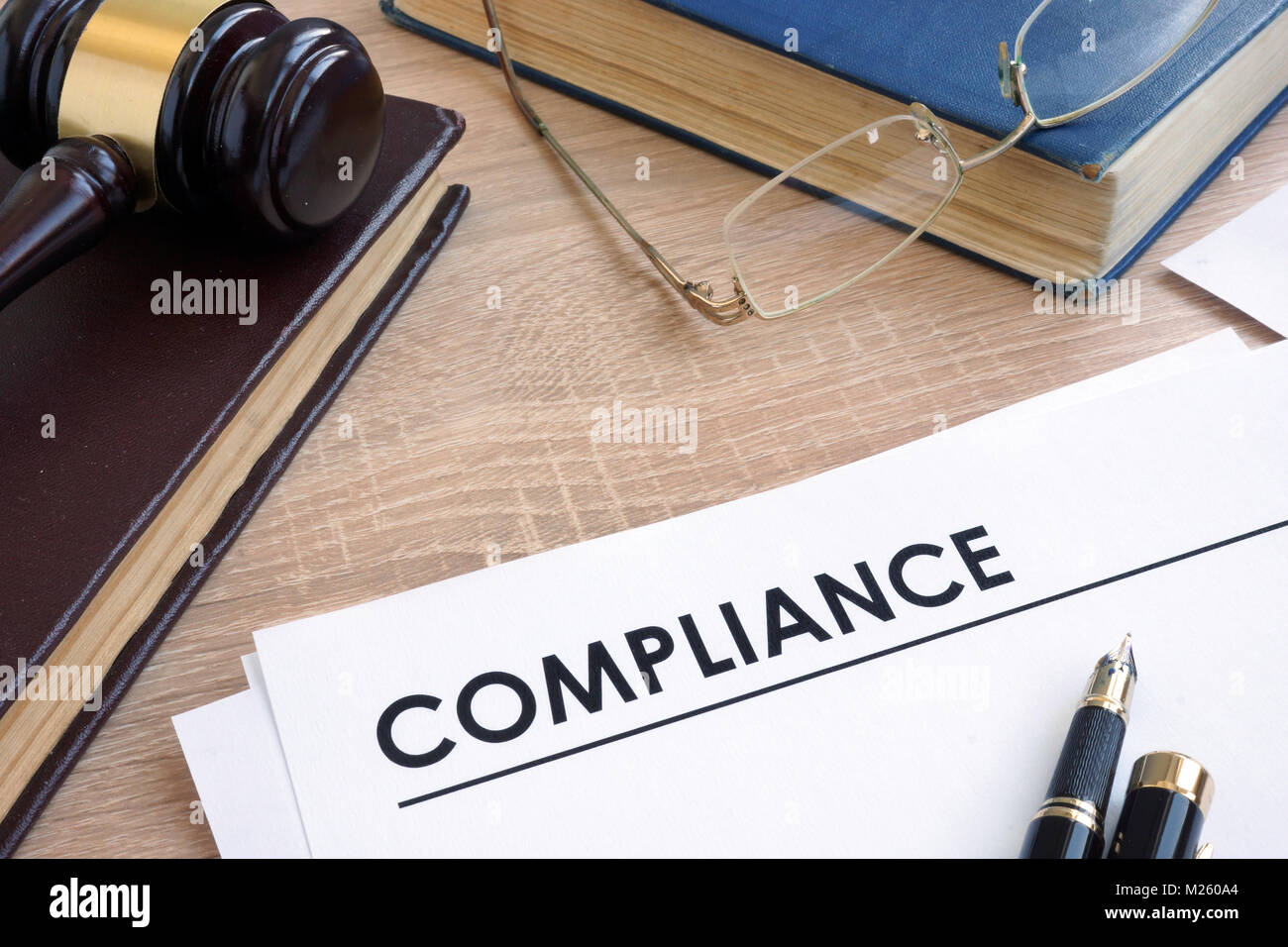Compliance on a wooden desk with books. - Stock Image