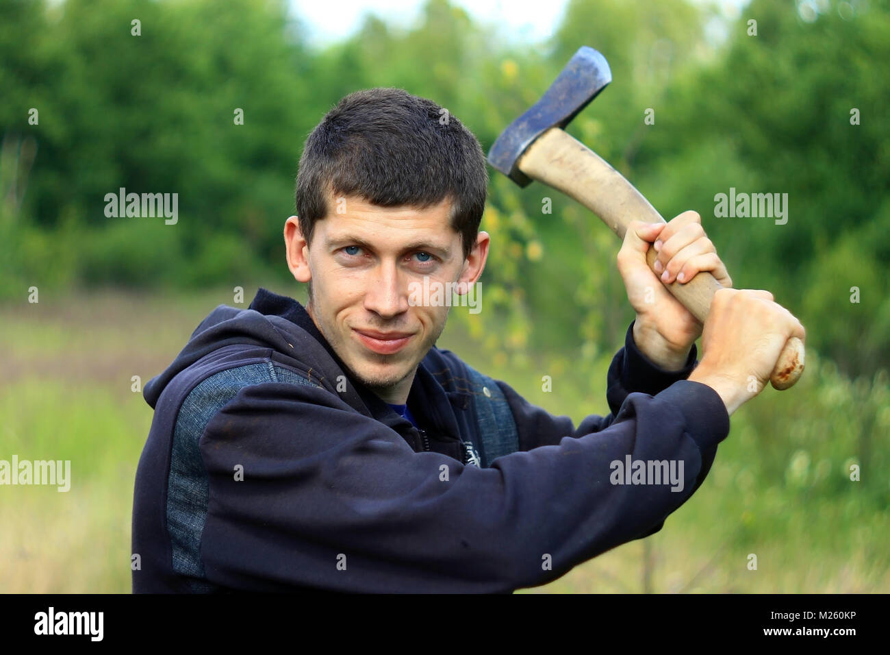 Young man with an axe chopping someone in summer forest - Stock Image