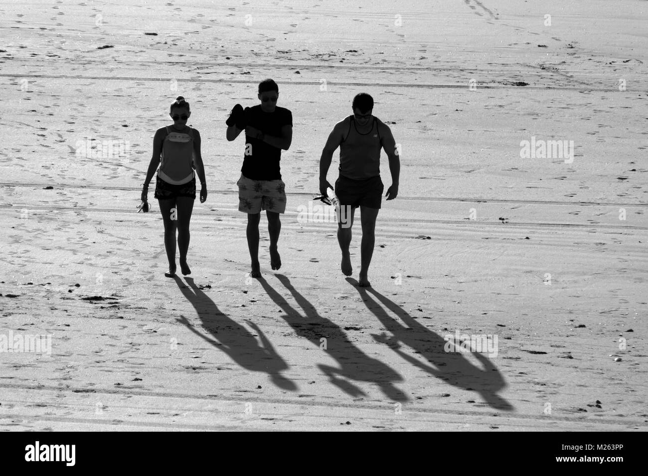 Silhouette of 3 people walking on a sandy beach, Cable Beach,  Broome, West Kimberley, Western Australia - Stock Image