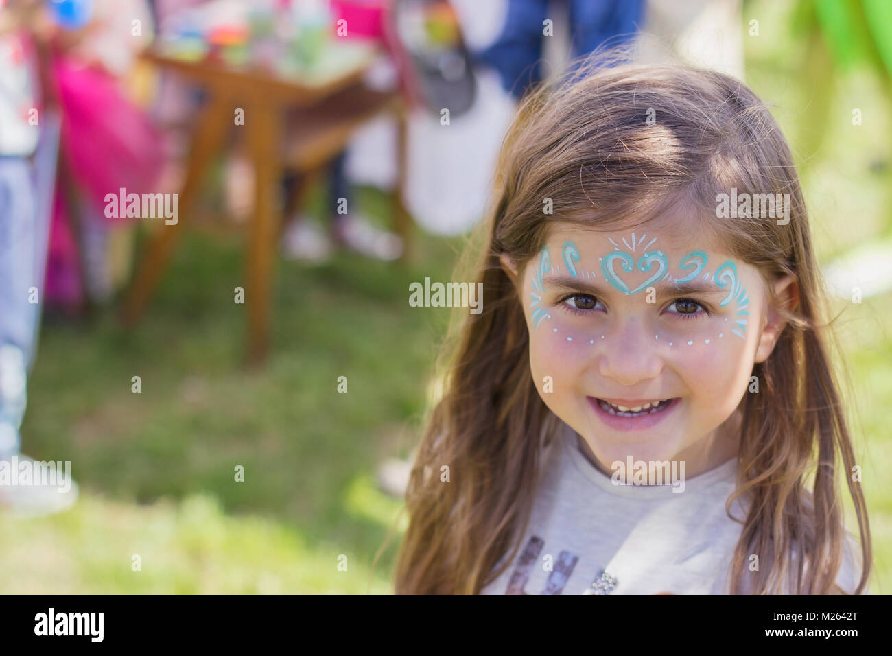 Outdoor portrait of a beautiful little girl with painted face - Stock Image