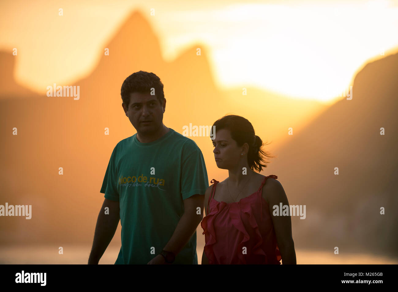 RIO DE JANEIRO - MARCH 20, 2017: A couple walks along the boardwalk at the Arpoador lookout point past a sunset - Stock Image