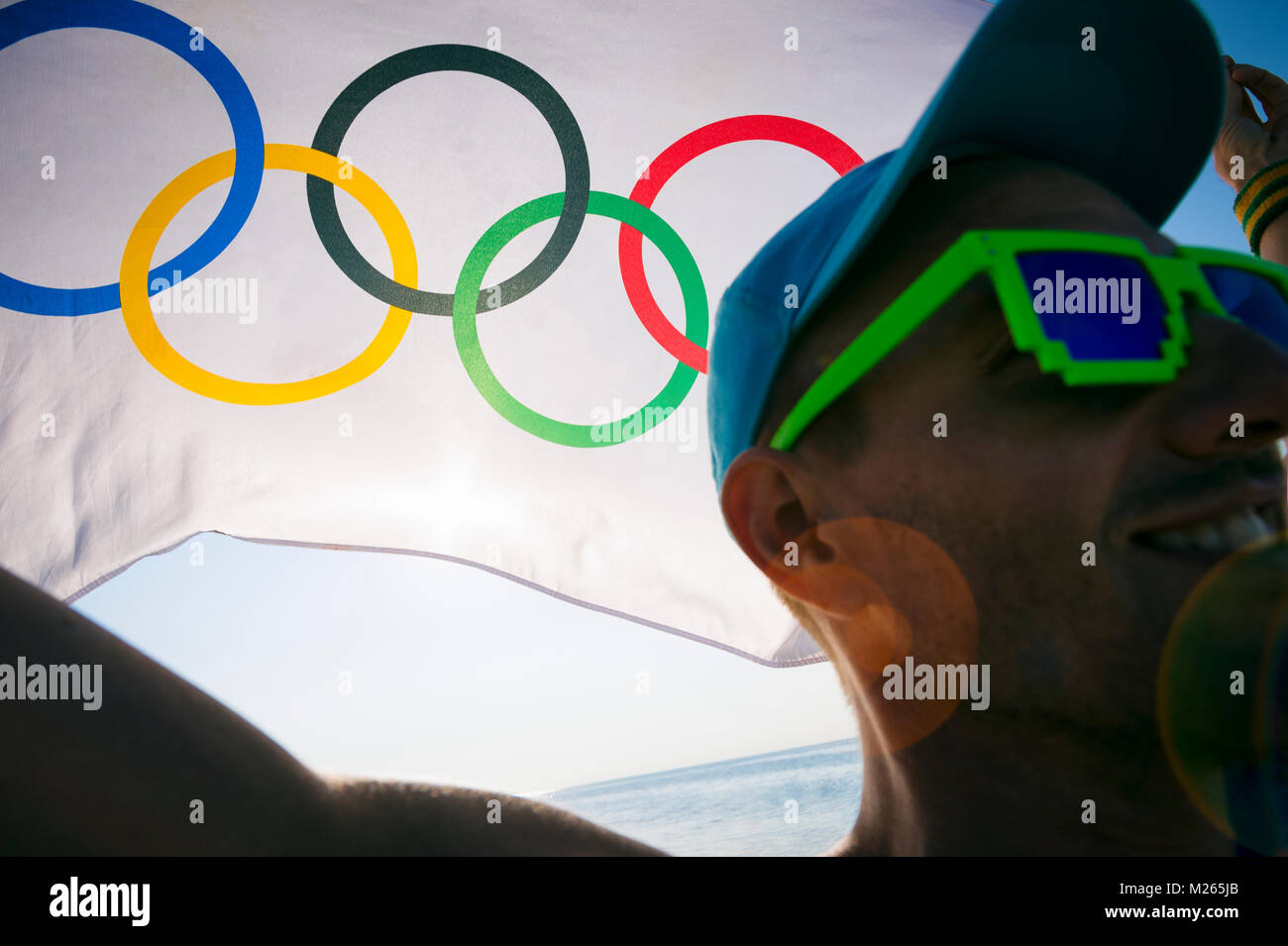 RIO DE JANEIRO - MARCH 10, 2016: Illustrative editorial of smiling Brazilian athlete holding Olympic flag at sunrise Stock Photo