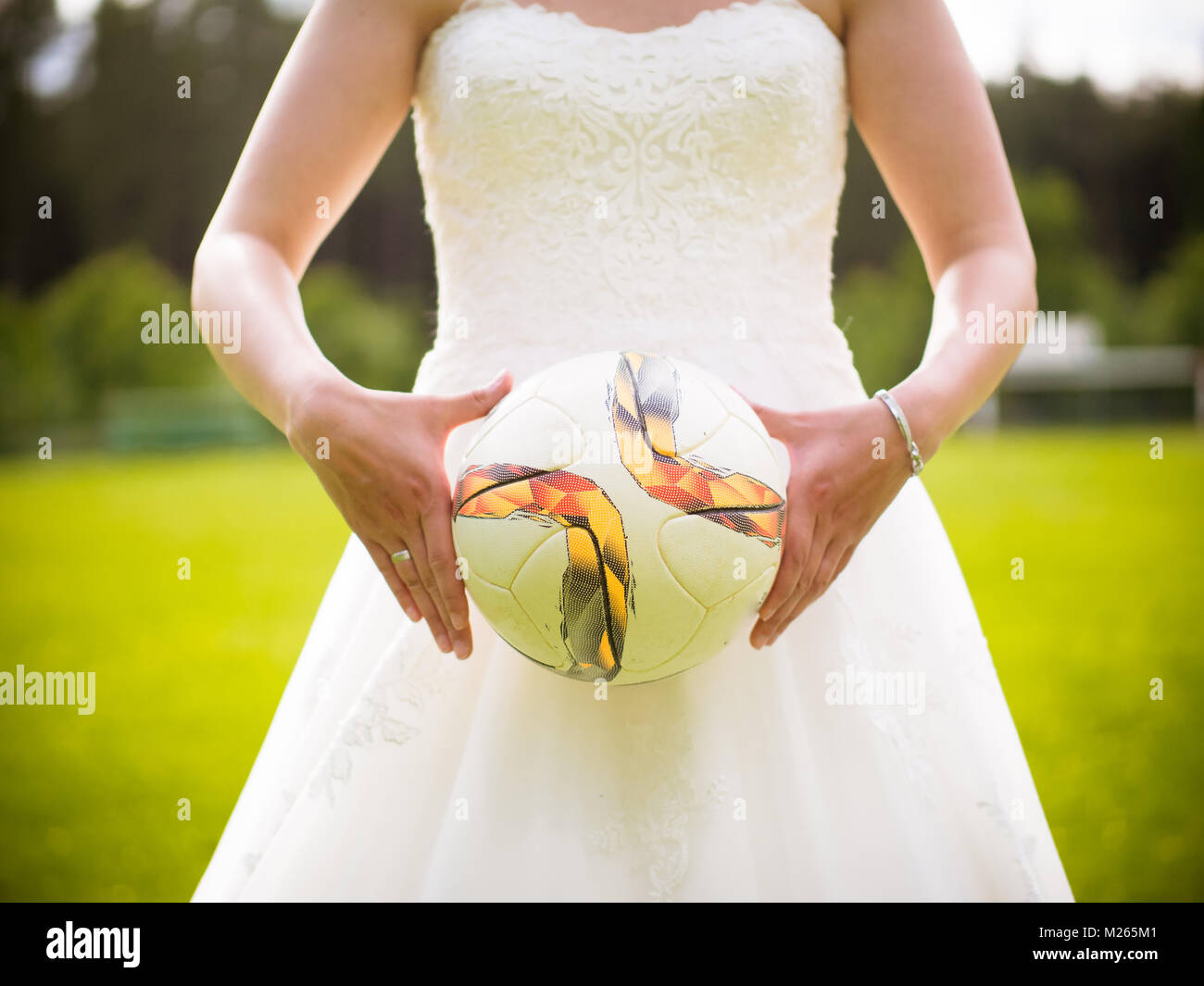 The bride holds the football in her hands - Stock Image