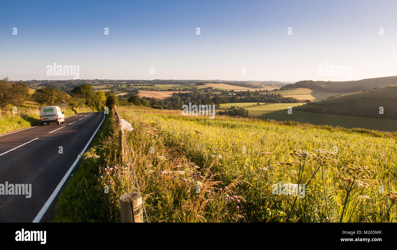 Traffic on the C13 Melbury Abbas road crosses the chalk grassland of Cranborne Chase between Blandford Forum and - Stock Image