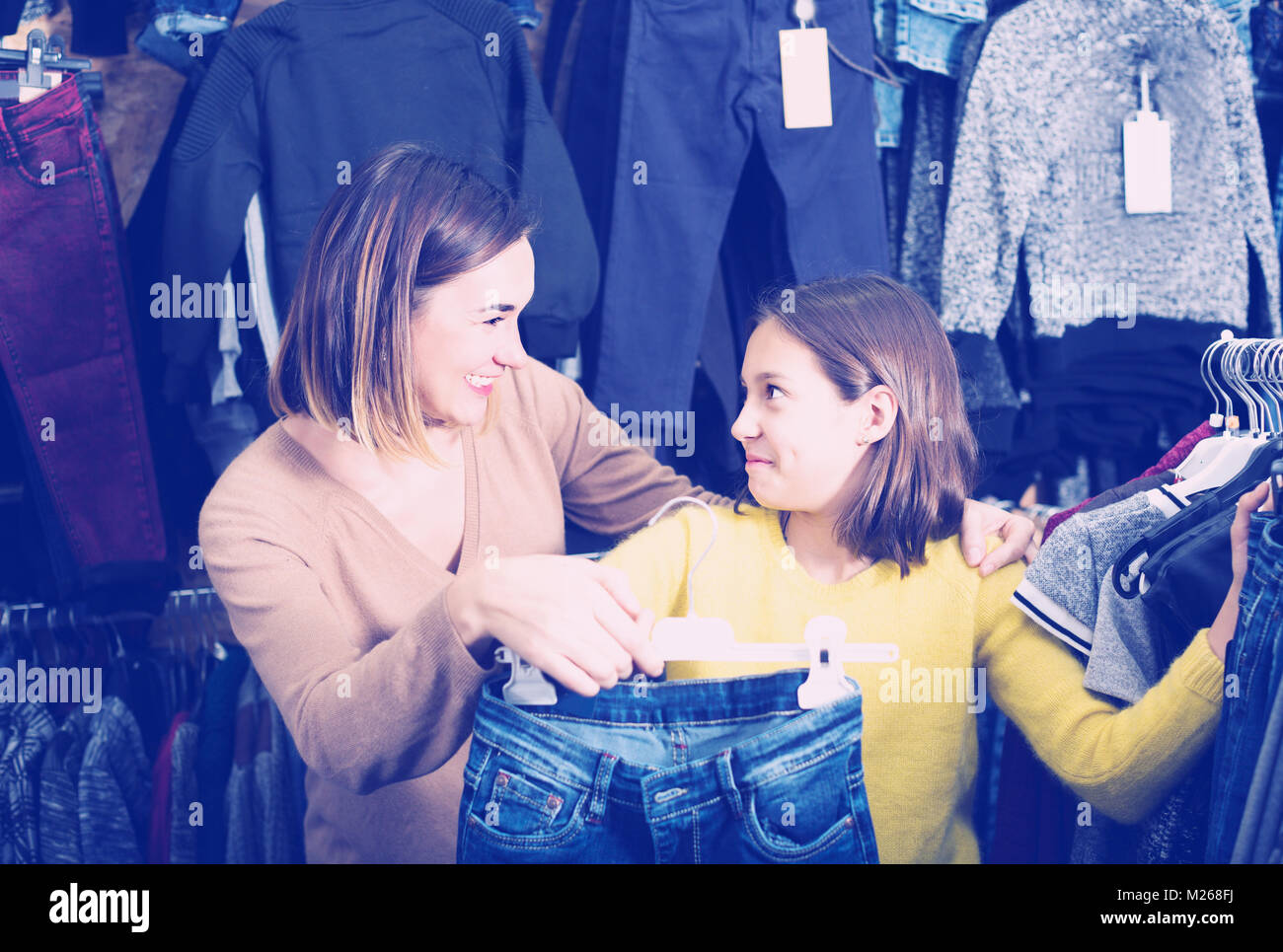 Mother and daughter are choosing trendy jeans in children's