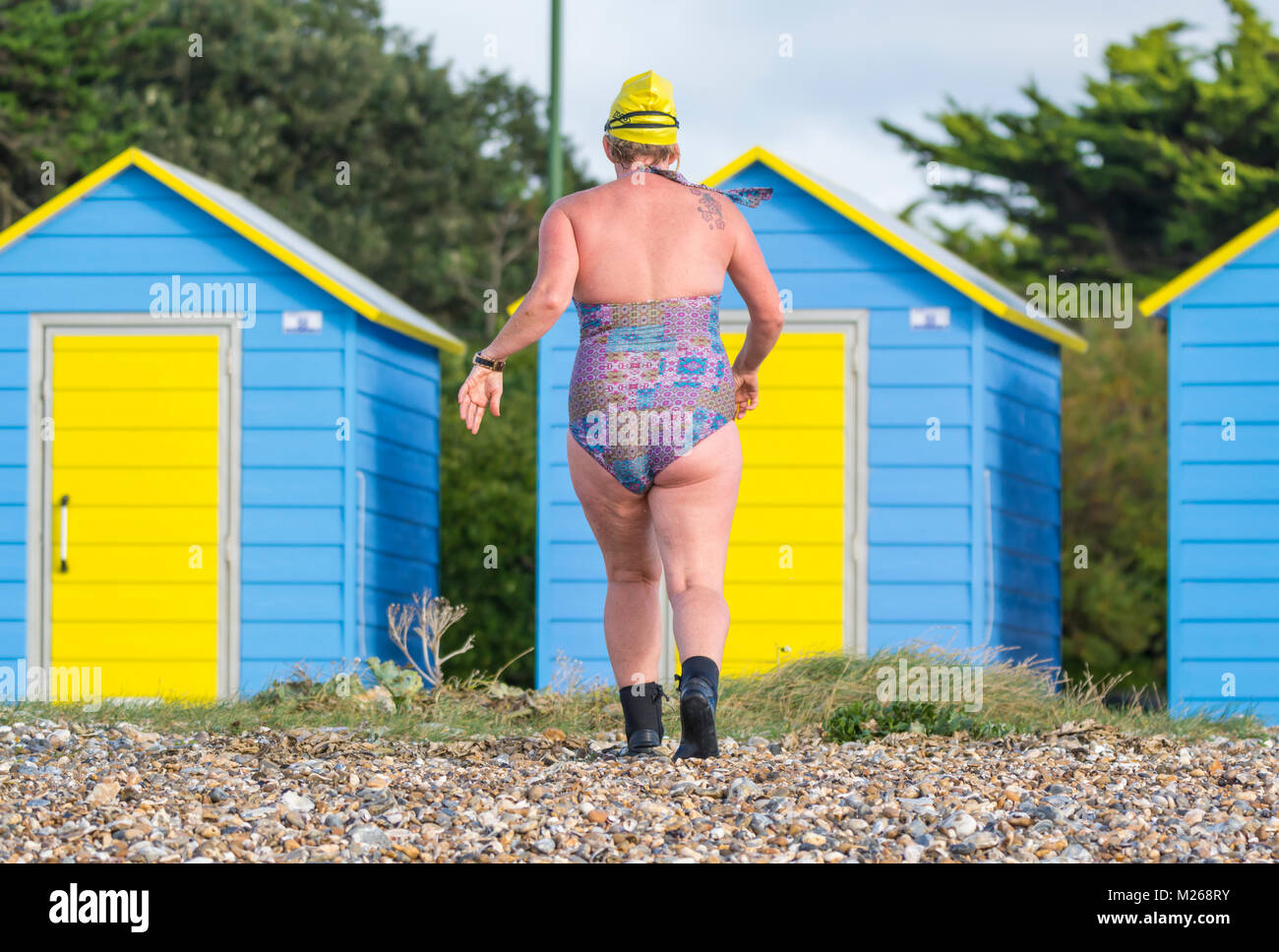 Woman in a one piece swimsuit after swimming in the sea on a cold day in the UK. - Stock Image