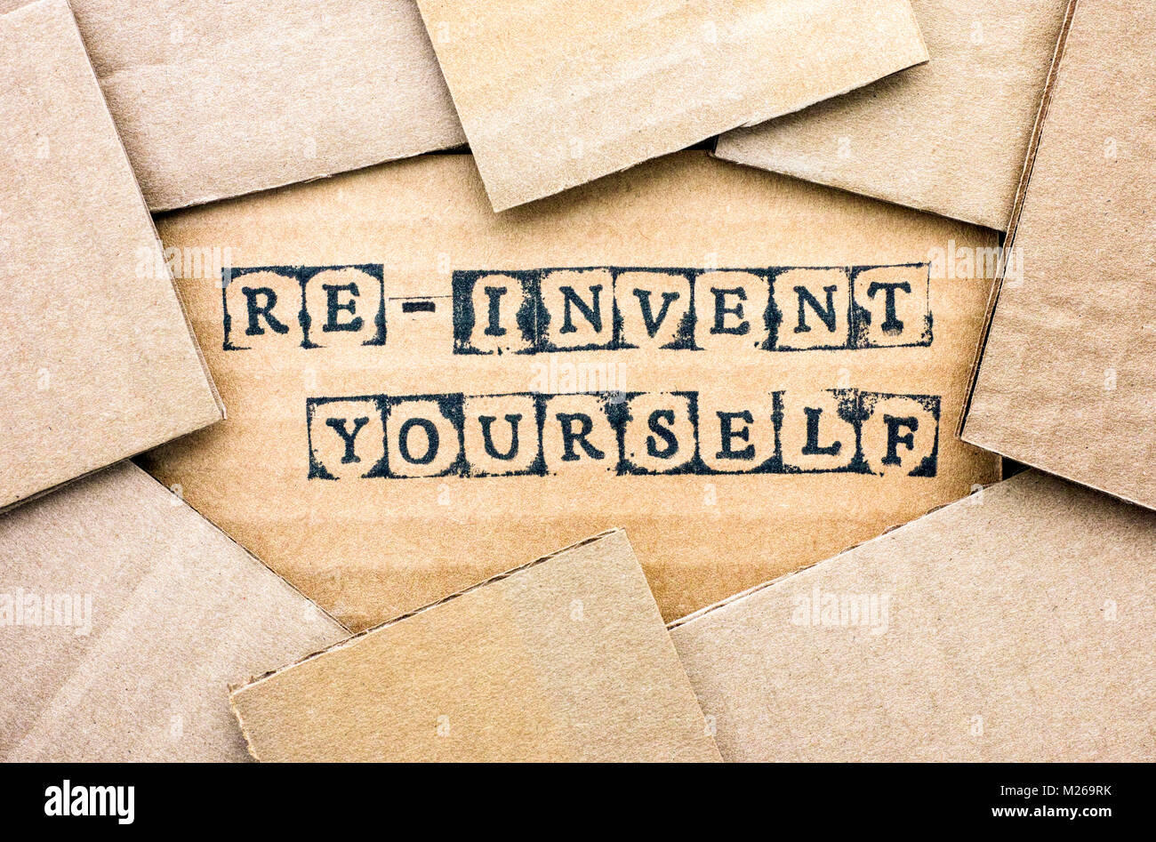 Words Re-invent Yourself make by black alphabet stamps on cardboard with some piece of cardboard. - Stock Image