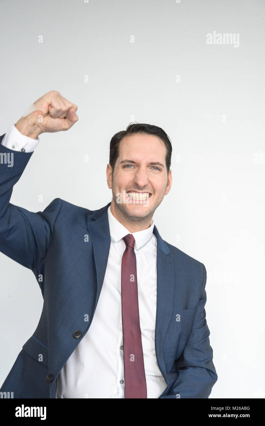 Portrait of a smartly dressed good looking man smiling and happy looking into camera and punching the air with joy. - Stock Image