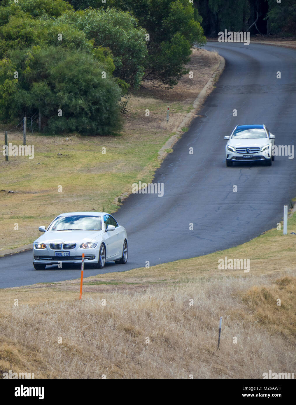 A white Mercedes GLA 180  and a white BMW vehicles driving on a country road in Margaret River, WA, Australia. - Stock Image