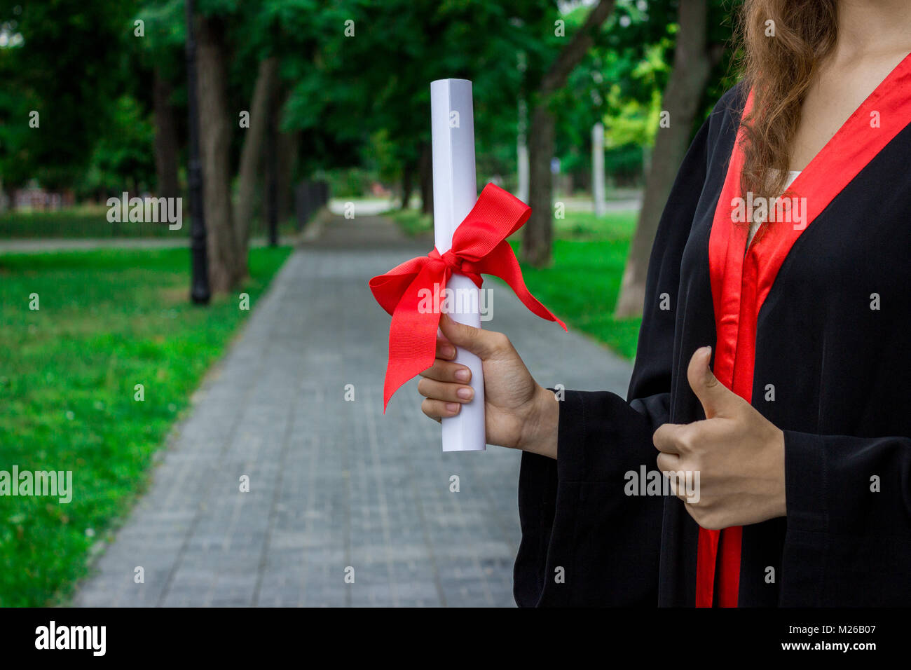 Graduate put her hands up and celebrating with certificate in her hand and feeling so happiness in Commencement - Stock Image