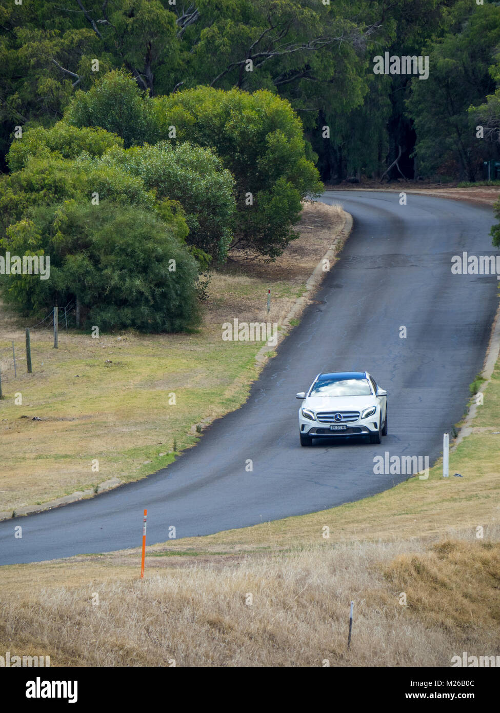 A white Mercedes GLA 180 vehicle driving on a country road in Margaret River, WA, Australia. - Stock Image