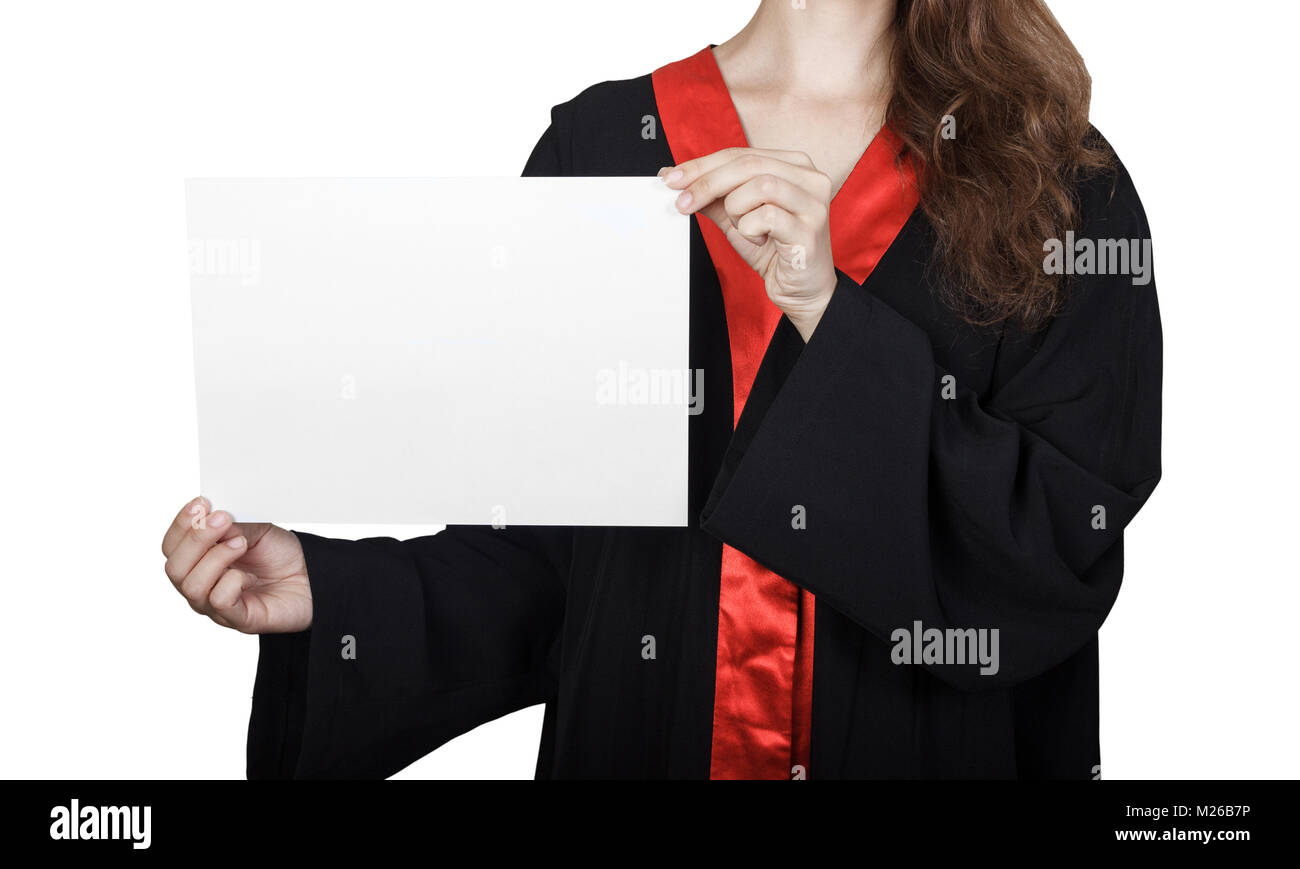 Female graduate student peeking from behind a blank panel. Portrait of happy girl in graduation gown with placard - Stock Image