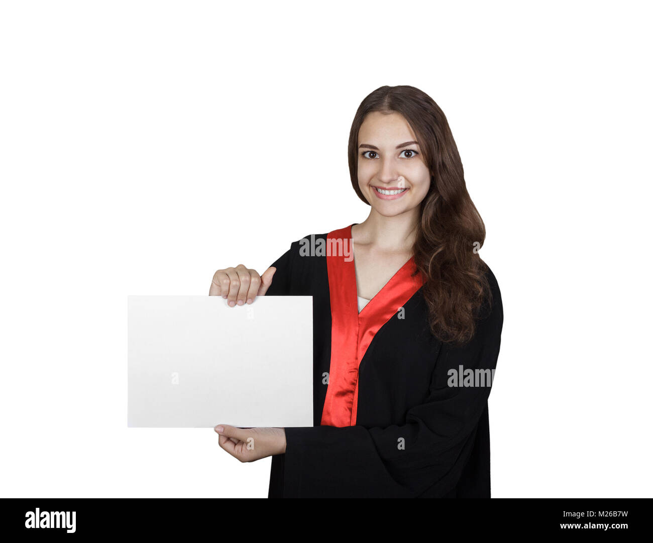 Beautiful graduate girl student in mantle showing blank placard board, isolated on white background. - Stock Image