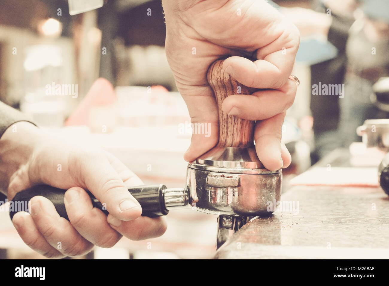 Barista presses ground coffee using tamper. Shallow depth of field, pastel color toning Stock Photo