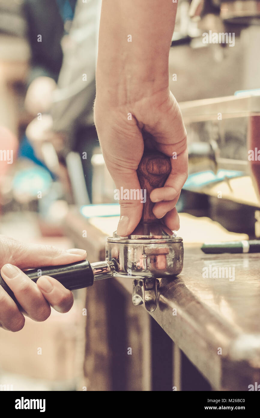 Female barista presses ground coffee using tamper. Shallow depth of field, pastel color toning Stock Photo