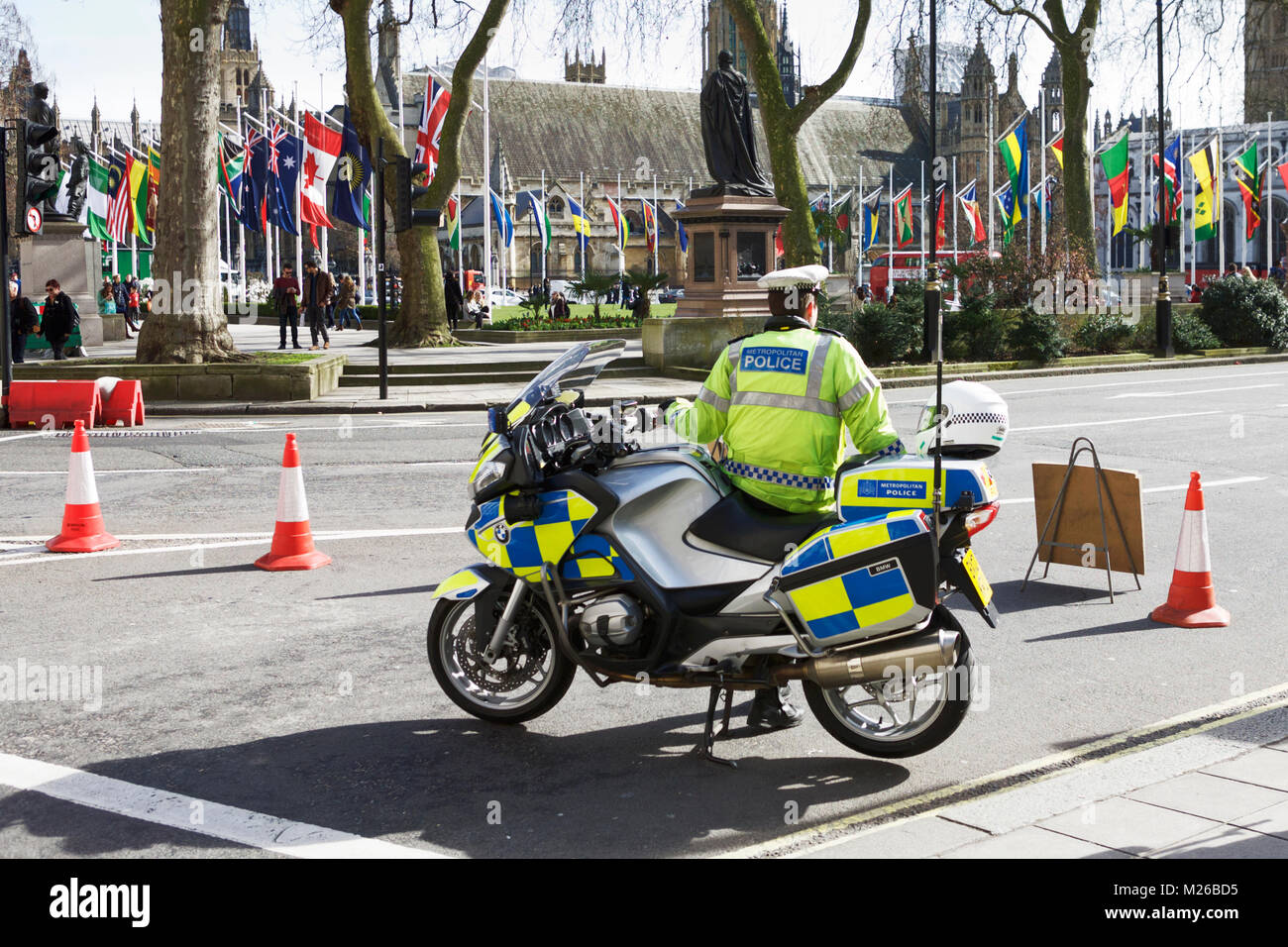 Metropolitan Police Motorcyclist, Parliament Square, London, UK. Commonwealth Day London. Commonwealth flags London. - Stock Image