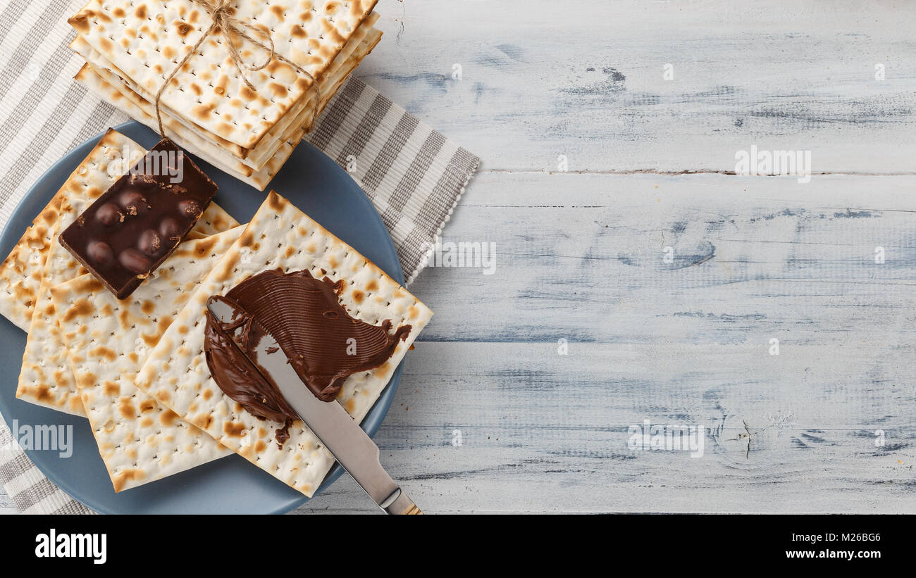 Jewish matzah bread with chocolate cream and knife. Tasty snack for Passover - Stock Image