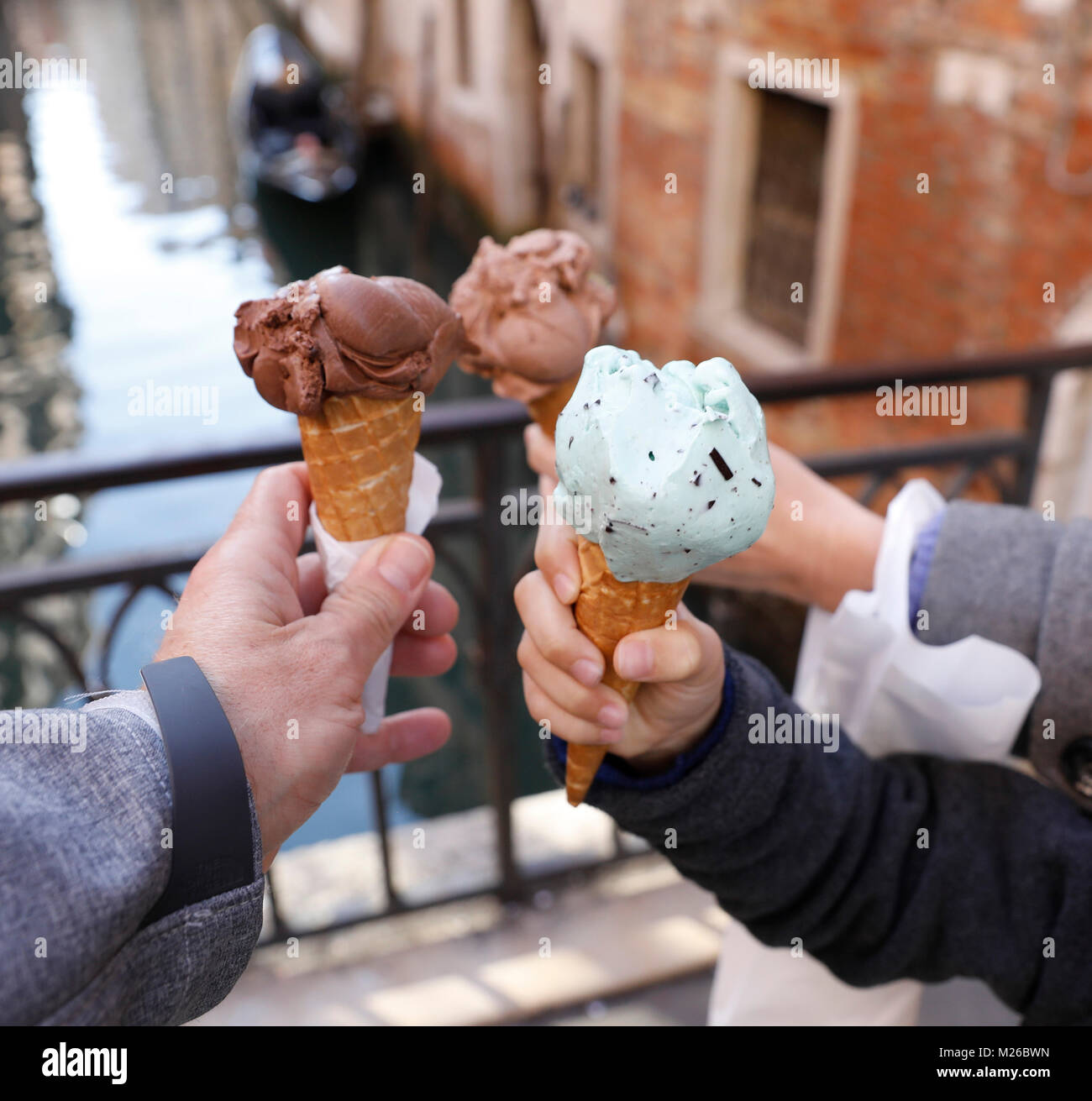 A family holds a variety of Italian Gelato next to a canal in Venice, Italy. (Photo by Matt May/Alamy) - Stock Image