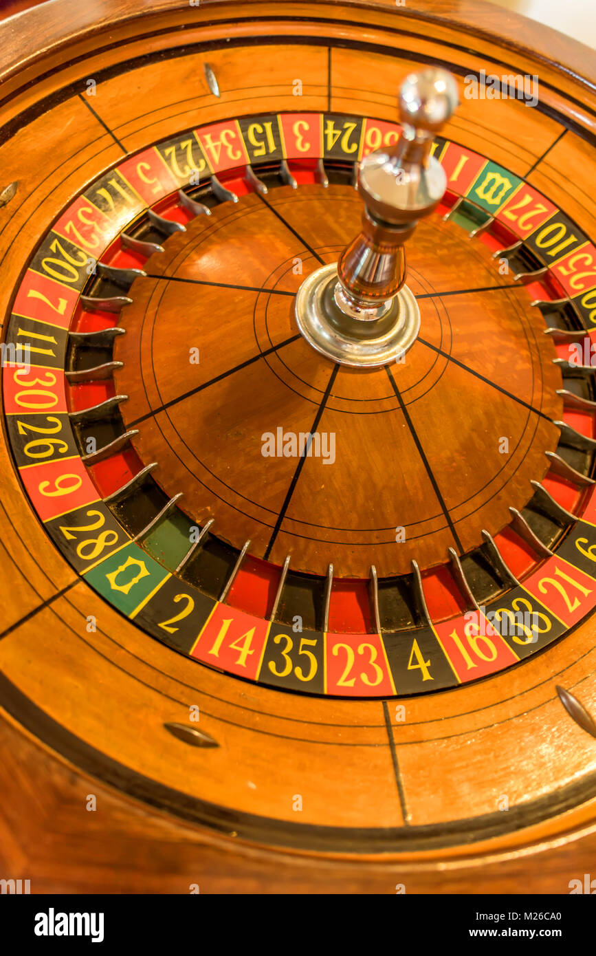 Round, wooden roulette wheel with numbers in a circle of a yellow wheel - Stock Image