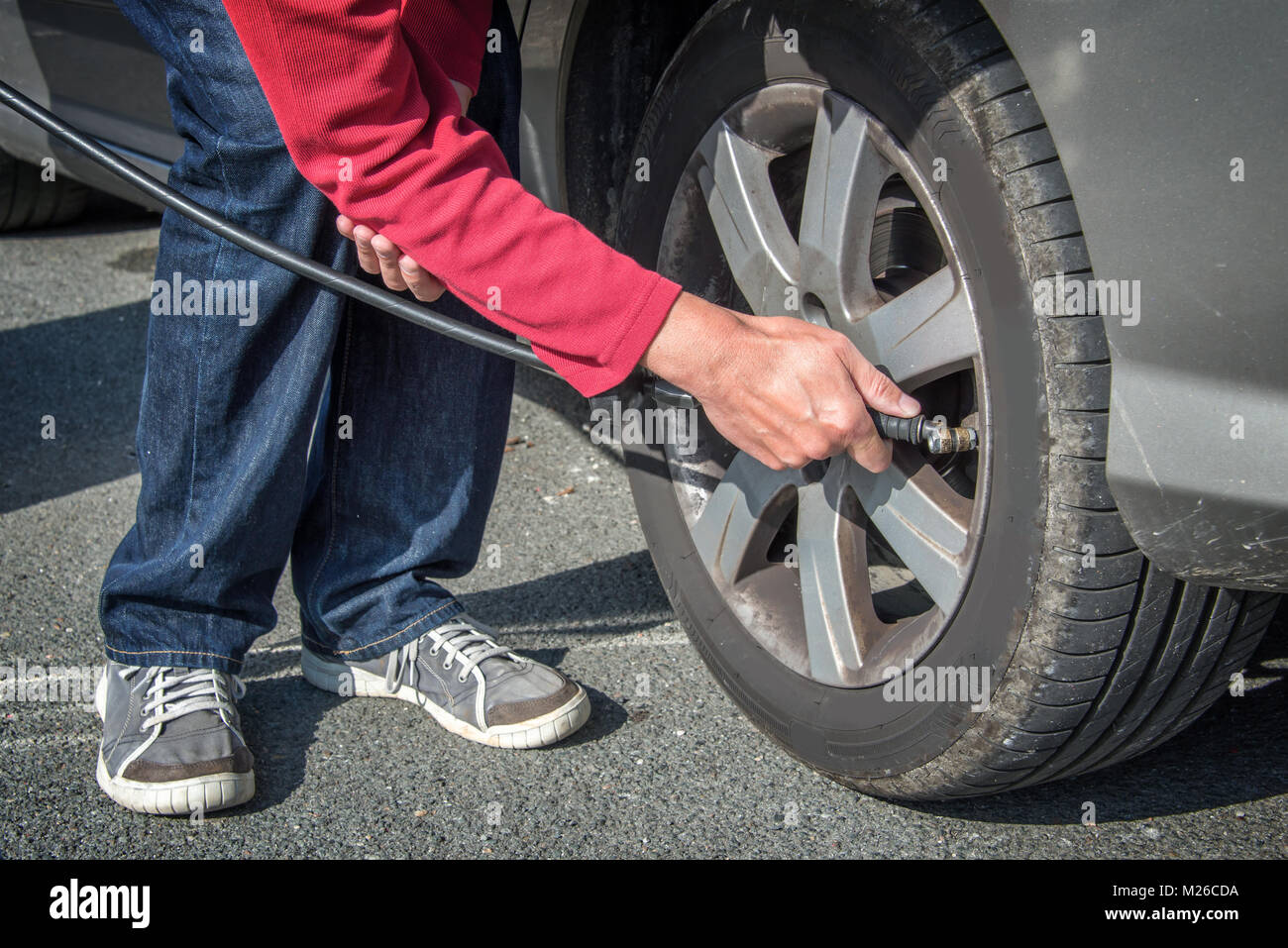 Driver checking air pressure and filling air in a tire of a car - Stock Image
