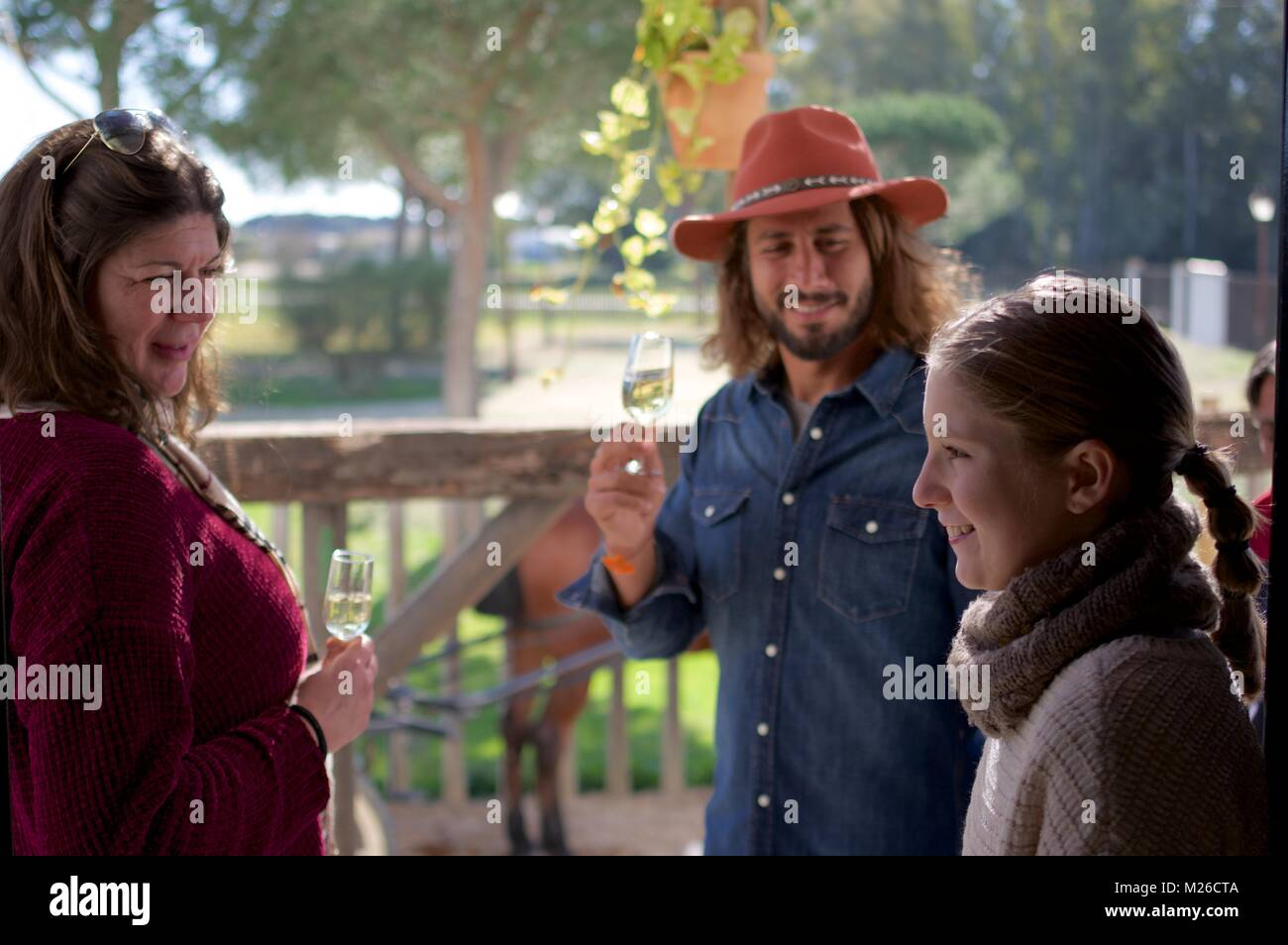 Adults drinking win in the presence of a young girl - Stock Image