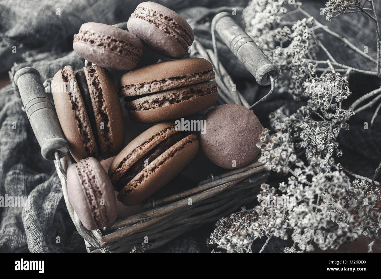 Freshly baked macaroons in wicker basket with handles with small white flowers on wooden background. - Stock Image