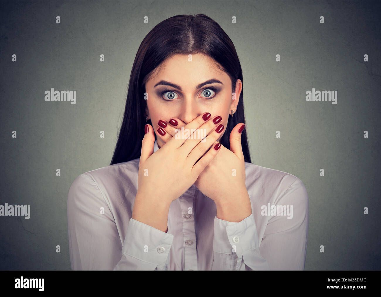 Young woman covering mouth looking terrified because of prohibition to talk. - Stock Image